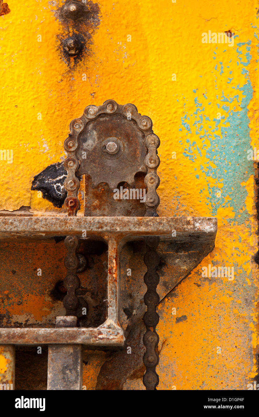 Gearwheel with transmission chain in a background with scratches rust and yellow paint on a plate of metal - Stock Image