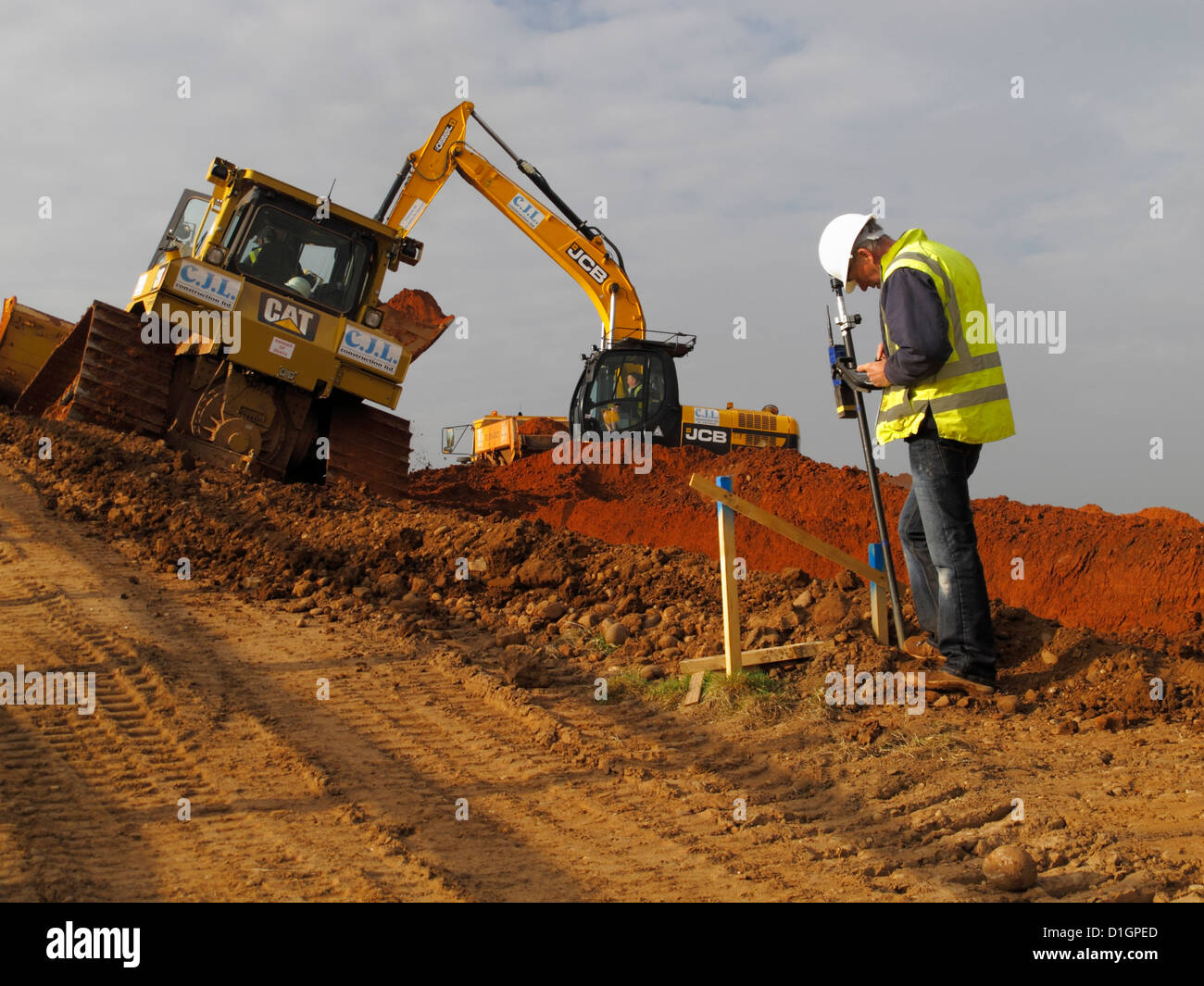Surveyor setting out engineer checks batter rail peg on UK new road construction site wearing high vis visibility - Stock Image