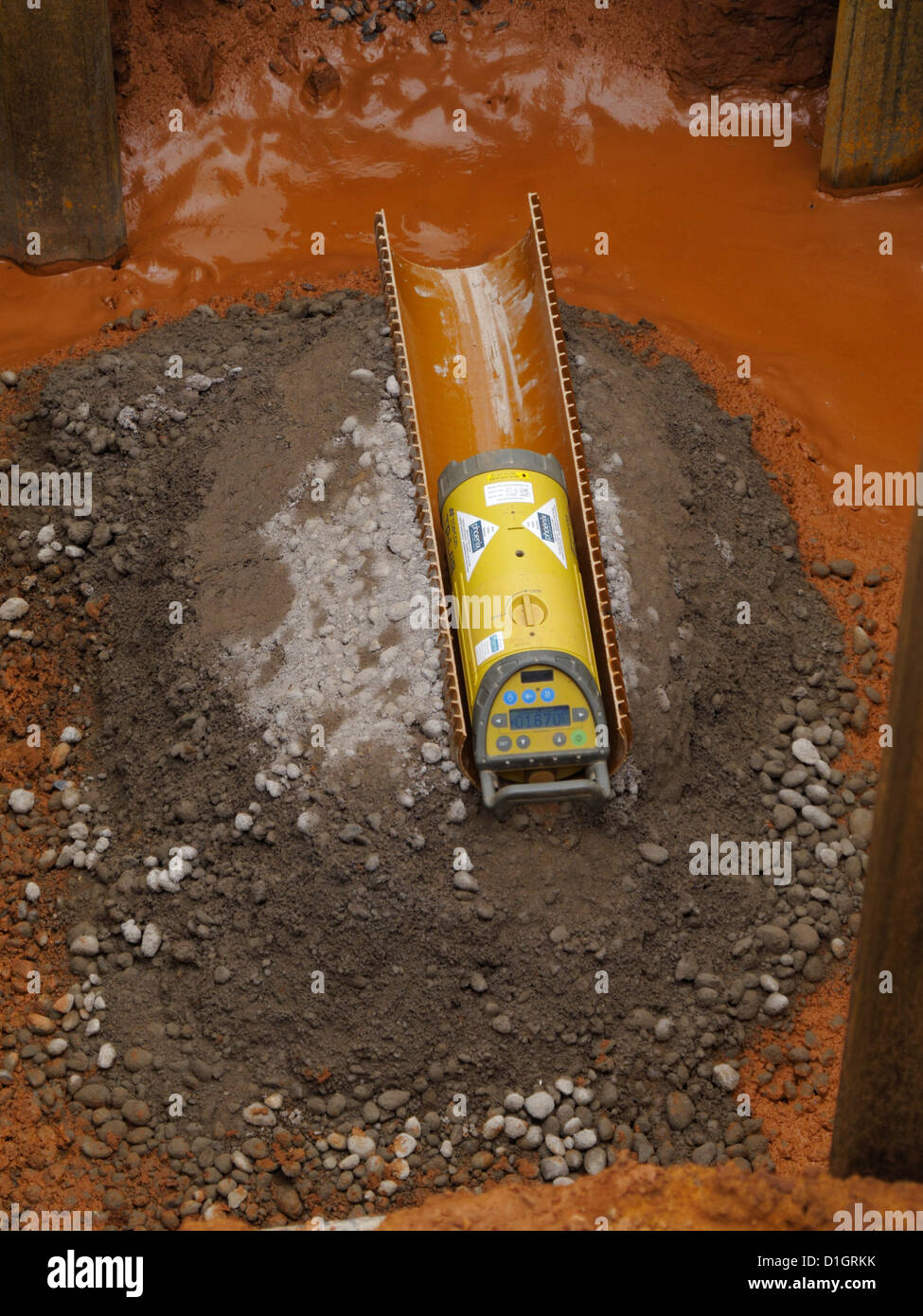 Laser pipe laying device for setting out drains in the invert of a manhole on a UK road construction site - Stock Image