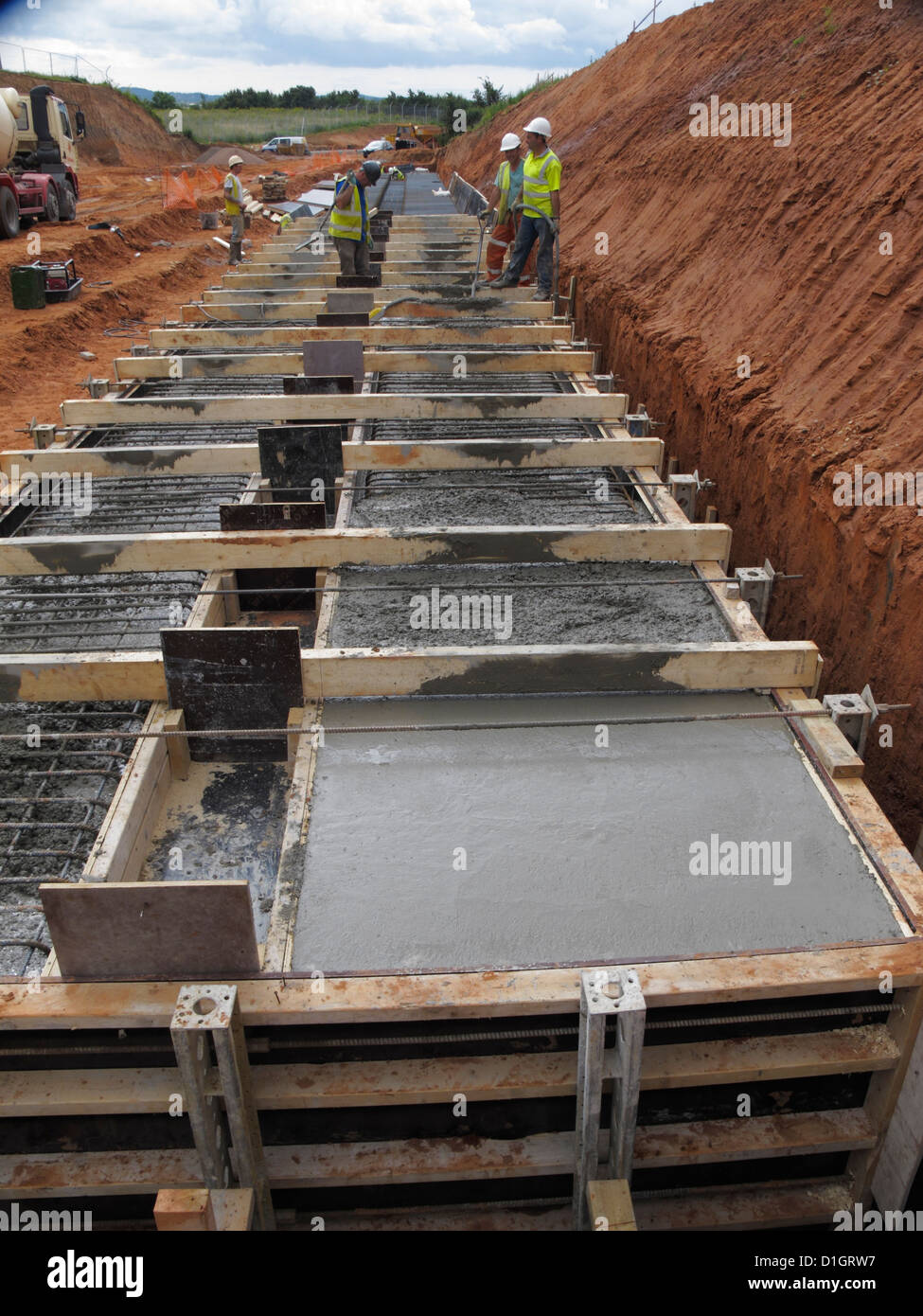 Pouring concrete for a reinforced concrete bridge foundation strip footing uk - Stock Image