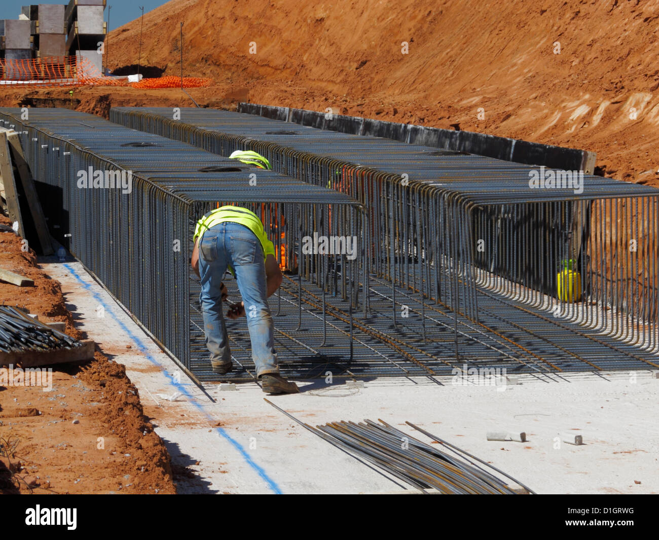 Steel fixer tying reinforcement bars in a bridge foundation base construction building site civil engineering UK - Stock Image