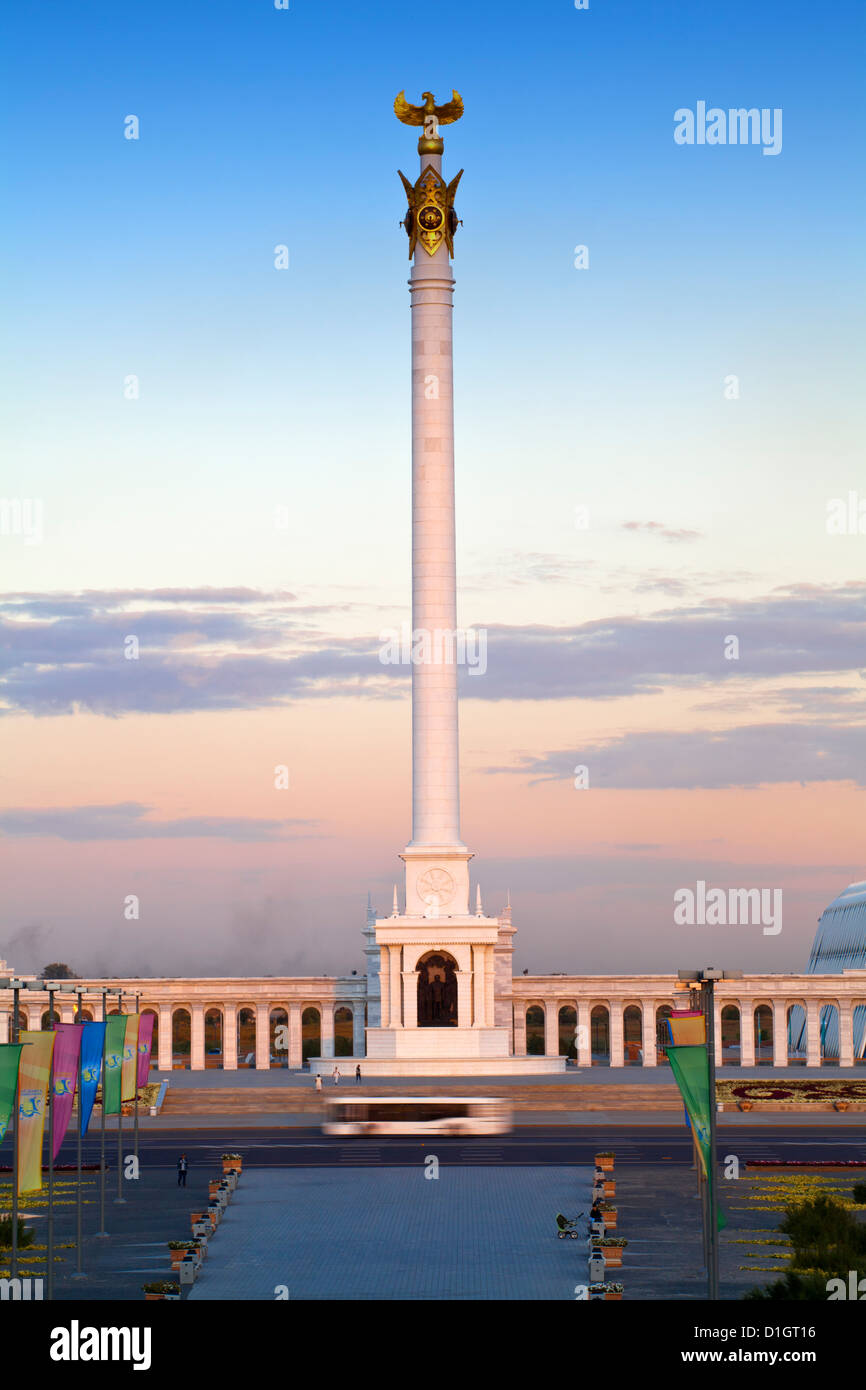 Bus passing KazakYeli monument (Kazakh Country) at dusk, Astana, Kazakhstan, Central Asia, Asia - Stock Image