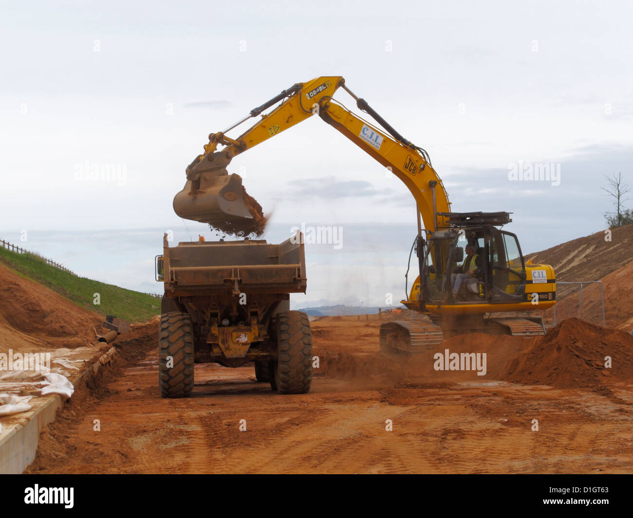 tracked backhoe digger loading large Volvo Dump truck site tipper Stock Photo: 52615979 - Alamy