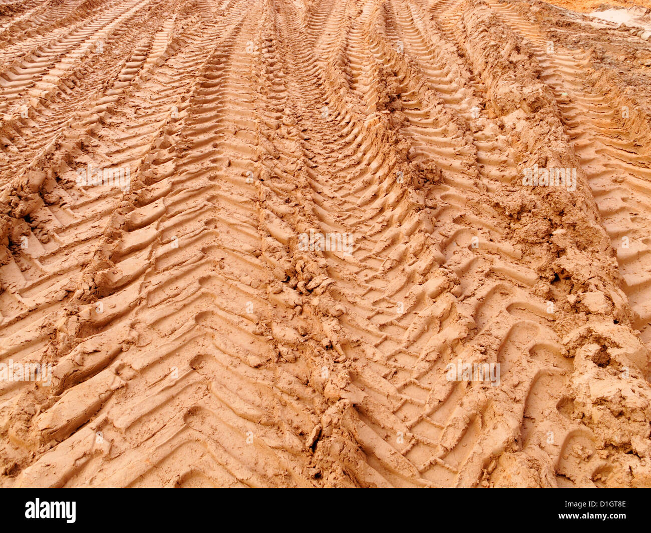 Pattern of tire tyre tracks track of deep treaded  construction vehicles in red soil mud earth of road construction - Stock Image