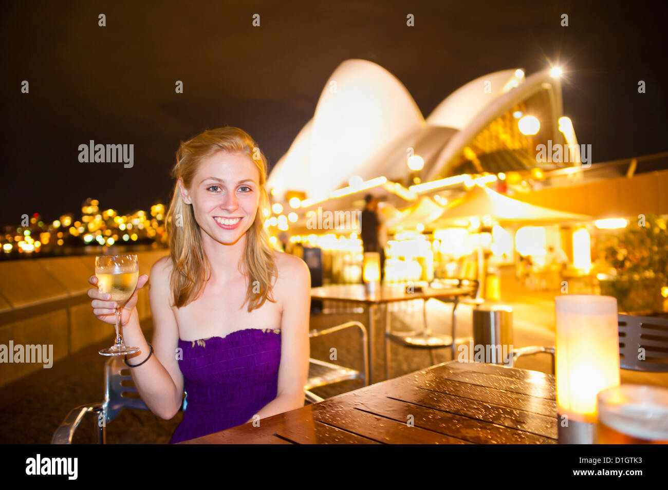 Young woman enjoying Sydney nightlife, having a drink at Opera Bar, Sydney Opera House, Sydney, New South Wales, - Stock Image