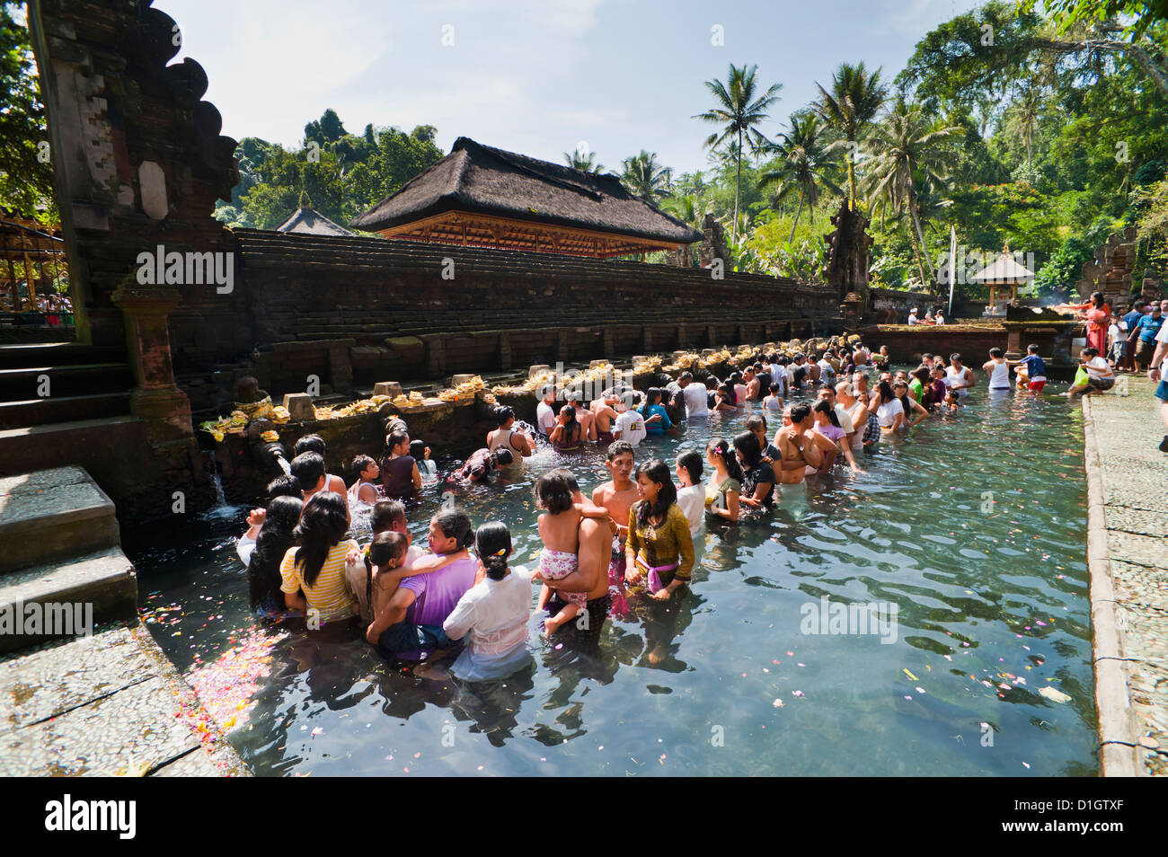 Balinese people in holy spring water in the sacred pool at Pura Tirta Empul Temple, Tampaksiring, Bali, Indonesia - Stock Image