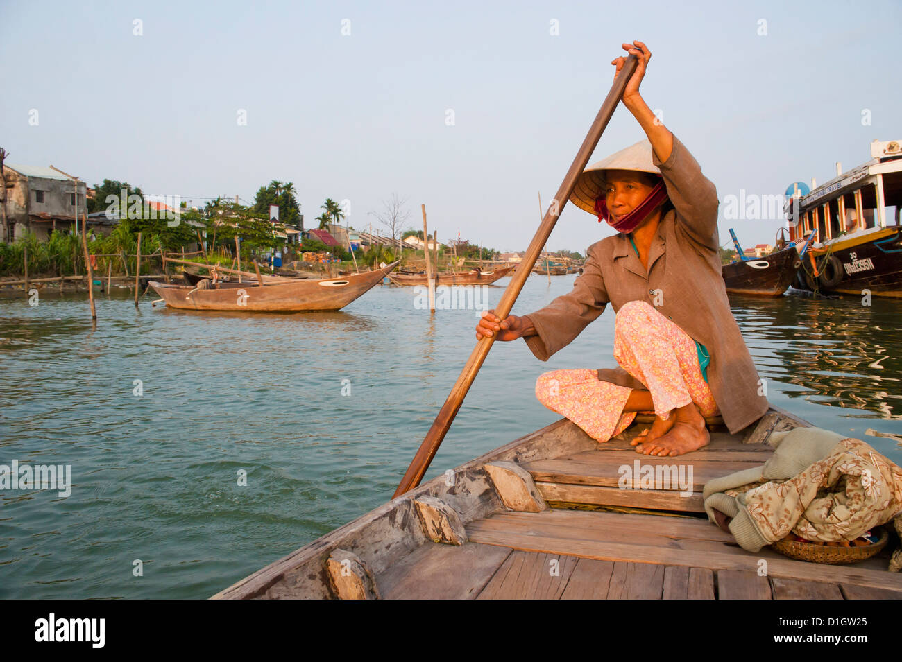 Old lady rowing in Hoi An Harbour, Vietnam, Indochina, Southeast Asia, Asia - Stock Image