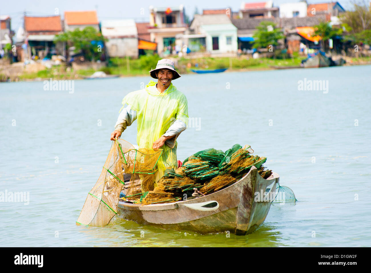 Man fishing from his boat at the old port town of Hoi An, Vietnam, Indochina, Southeast Asia, Asia - Stock Image