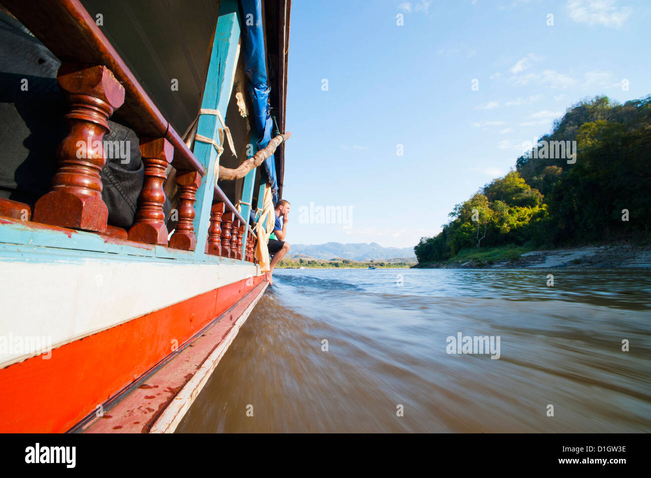 Tourist on the side of the slow boat from Thailand to Vientiane, Laos, Indochina, Southeast Asia, Asia - Stock Image