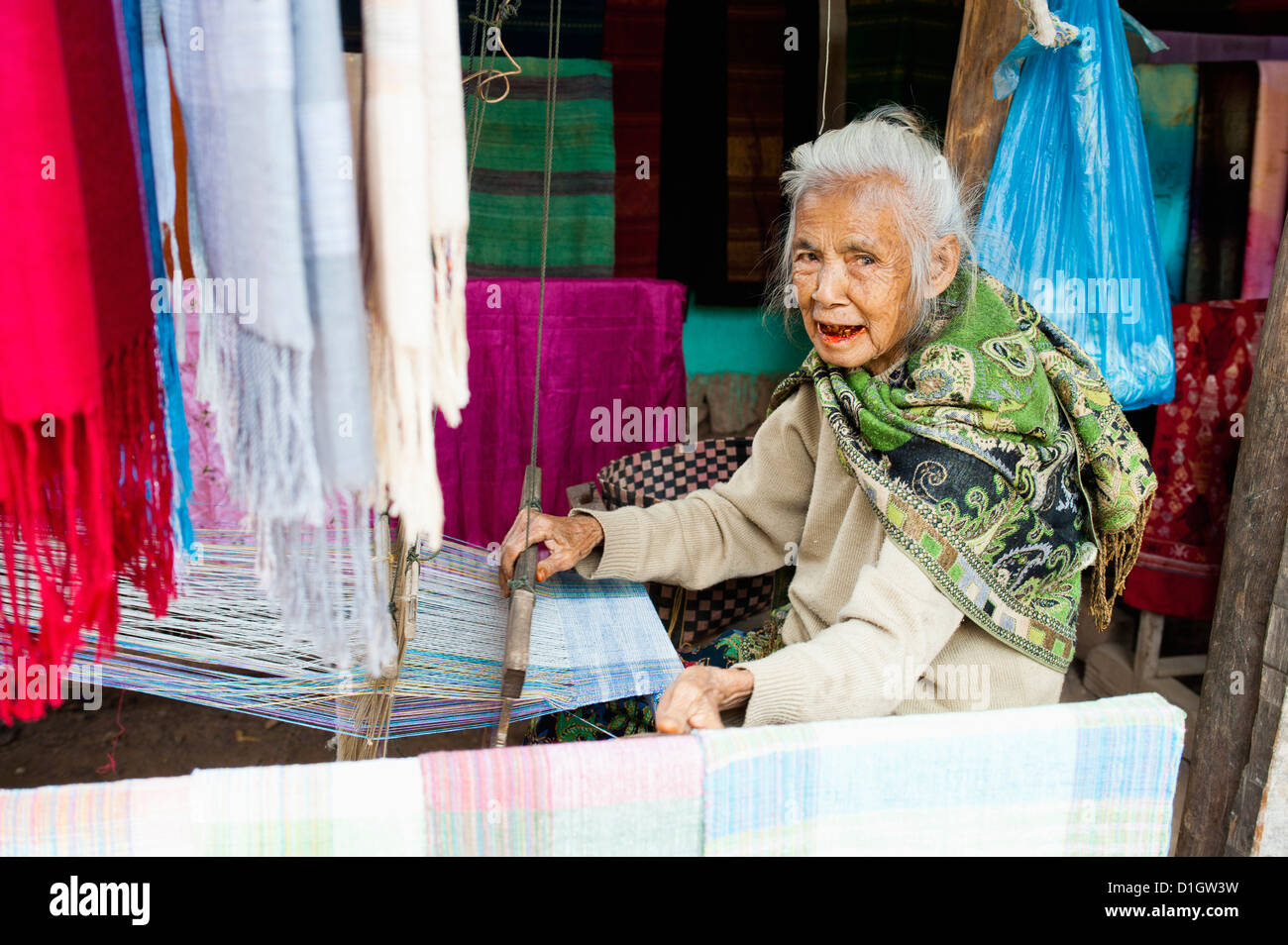 Old woman weaving scarves at her loom, Luang Prabang, Laos, Indochina, Southeast Asia, Asia - Stock Image