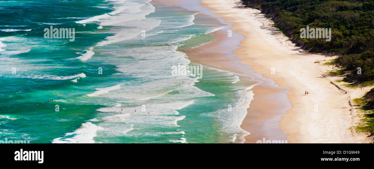 Panoramic photo of surfers heading out to surf on Tallow Beach at Cape Byron Bay, New South Wales, Australia, Pacific - Stock Image