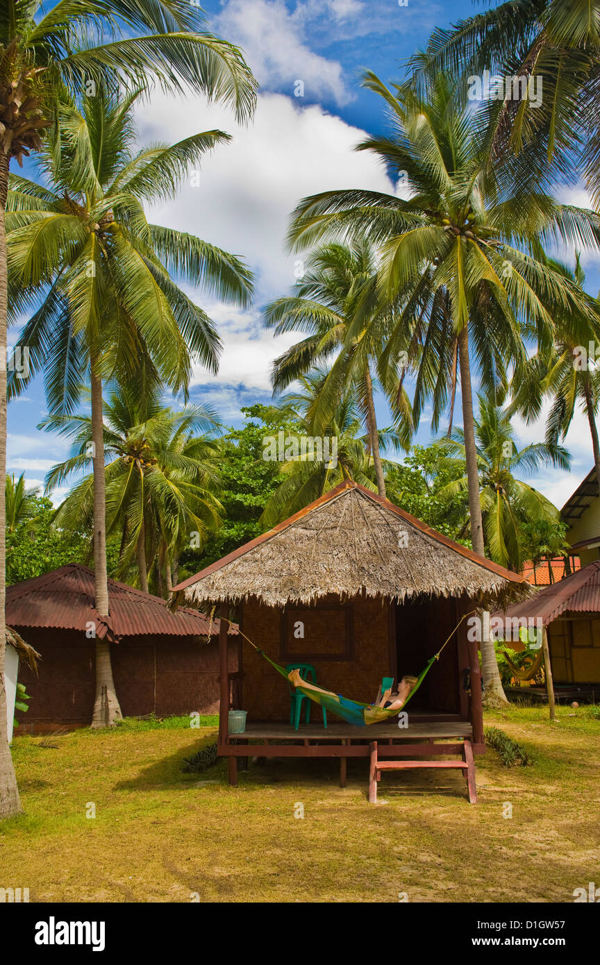 Tourist relaxing in a hammock on a bamboo beach hut on the Thai island of Koh Lanta, South Thailand, Southeast Asia, - Stock Image