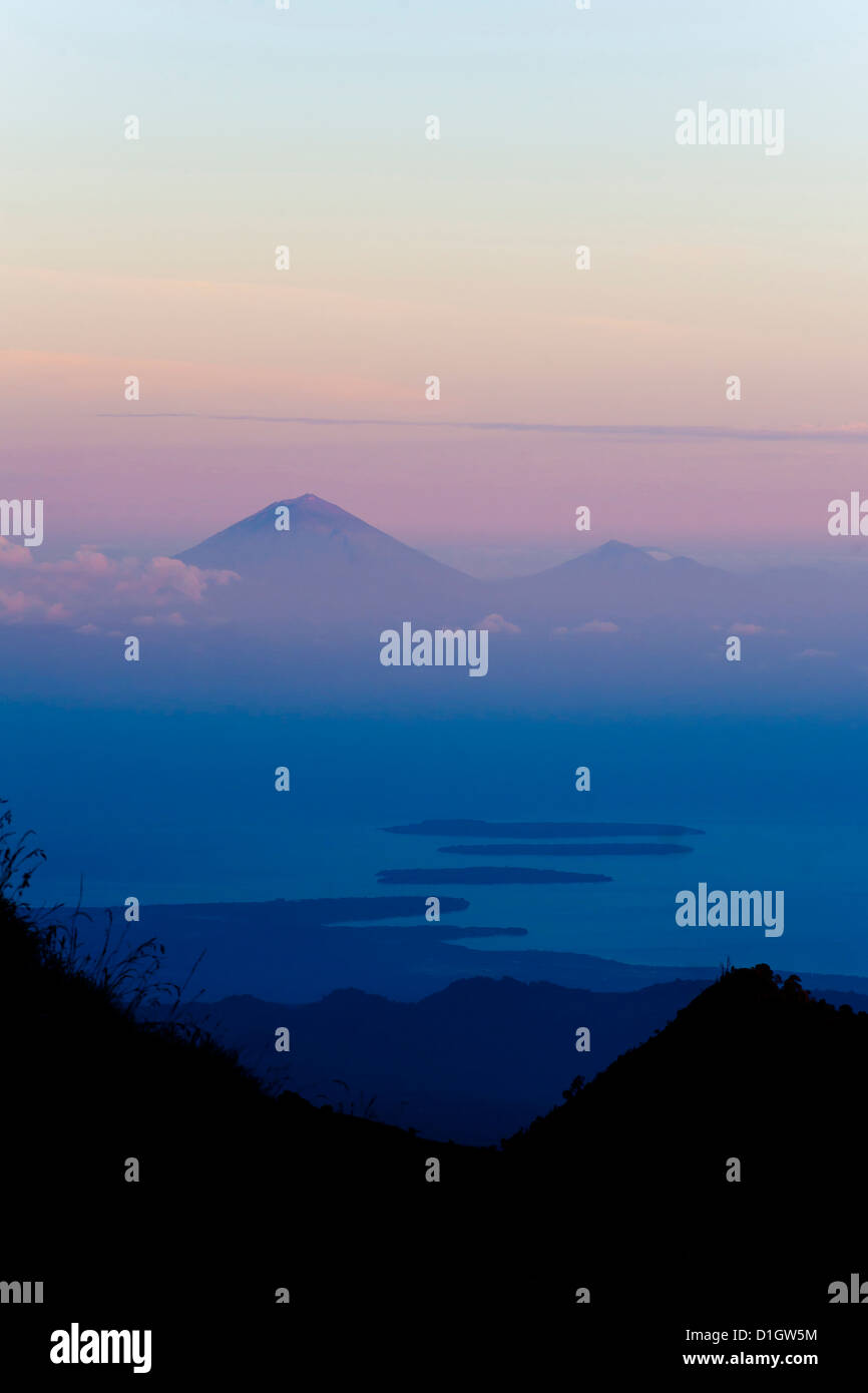 Sunset over Mount Agung and Mount Batur on Bali, and the Three Gili Isles taken from Mount Rinjani, Lombok, Indonesia - Stock Image
