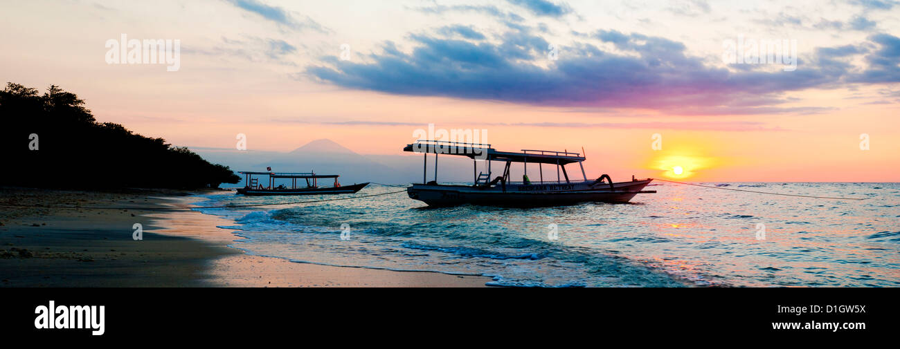 Mount Agung on Bali and fishing boats silhouetted against a sunset, Gili Trawangan, Gili Isles, Indonesia, Southeast - Stock Image