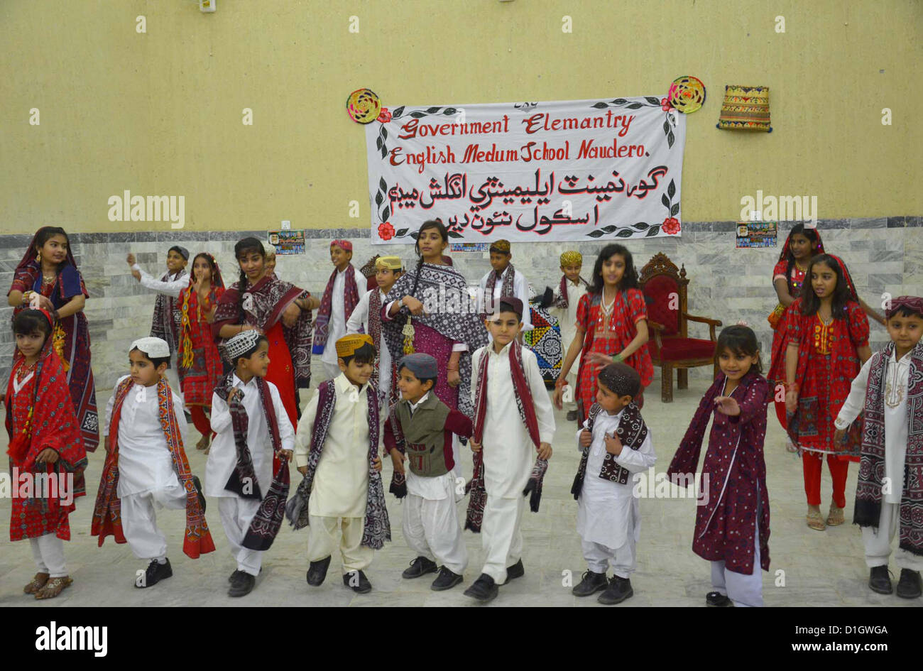 Students in traditional dresses are performing tableau on