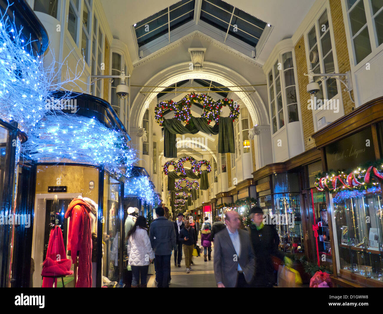 Burlington Arcade in Piccadilly with traditional Christmas decorations and shoppers with shopping bags London UK - Stock Image