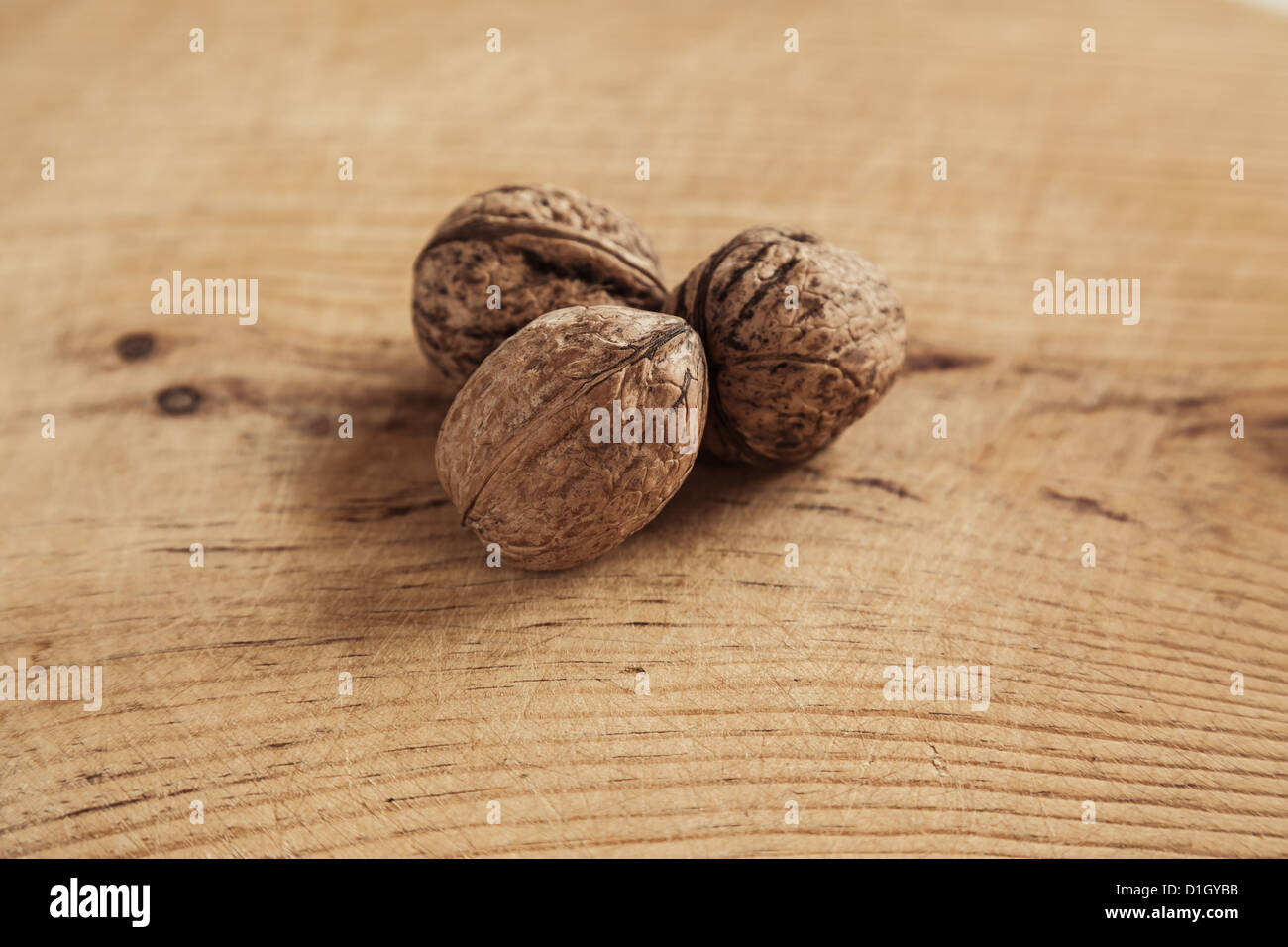 Three walnut on wooden background. Shallow depth of field. Stock Photo