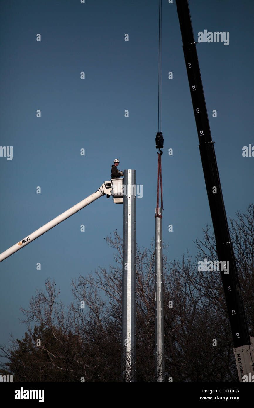 Man in bucket next to steel utility pole being installed. - Stock Image