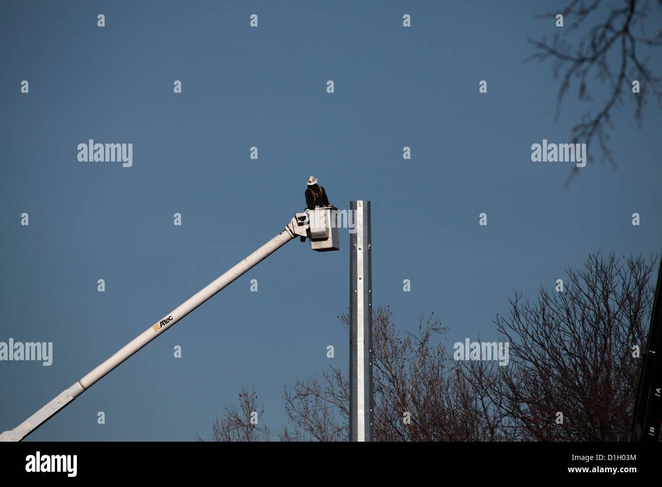 Man in bucket lift working on steel utility pole. - Stock Image