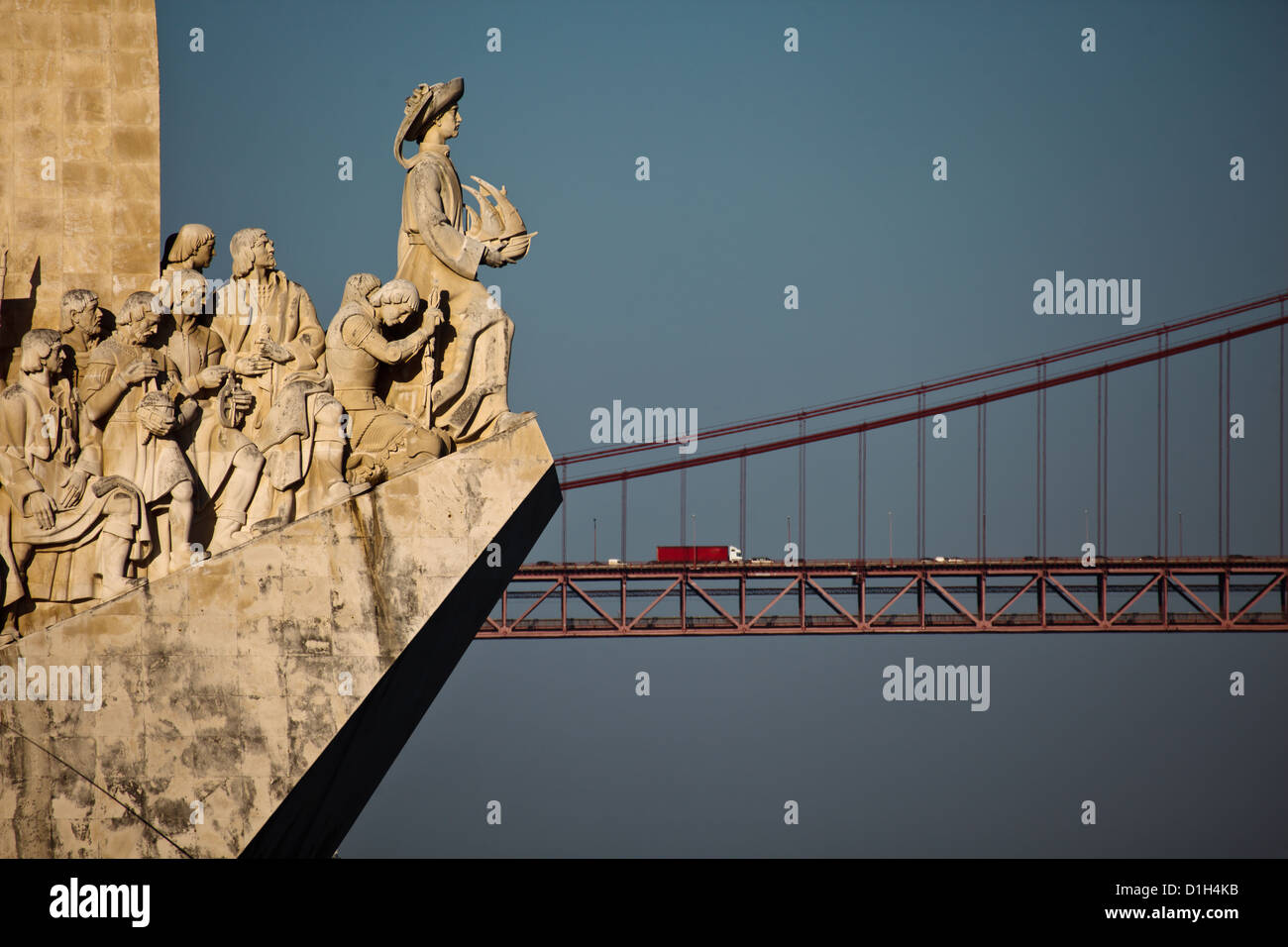 Closeup of Lisbon Portugal Monument to Discoveries explorers carved stone statues with the 25th of April bridge - Stock Image