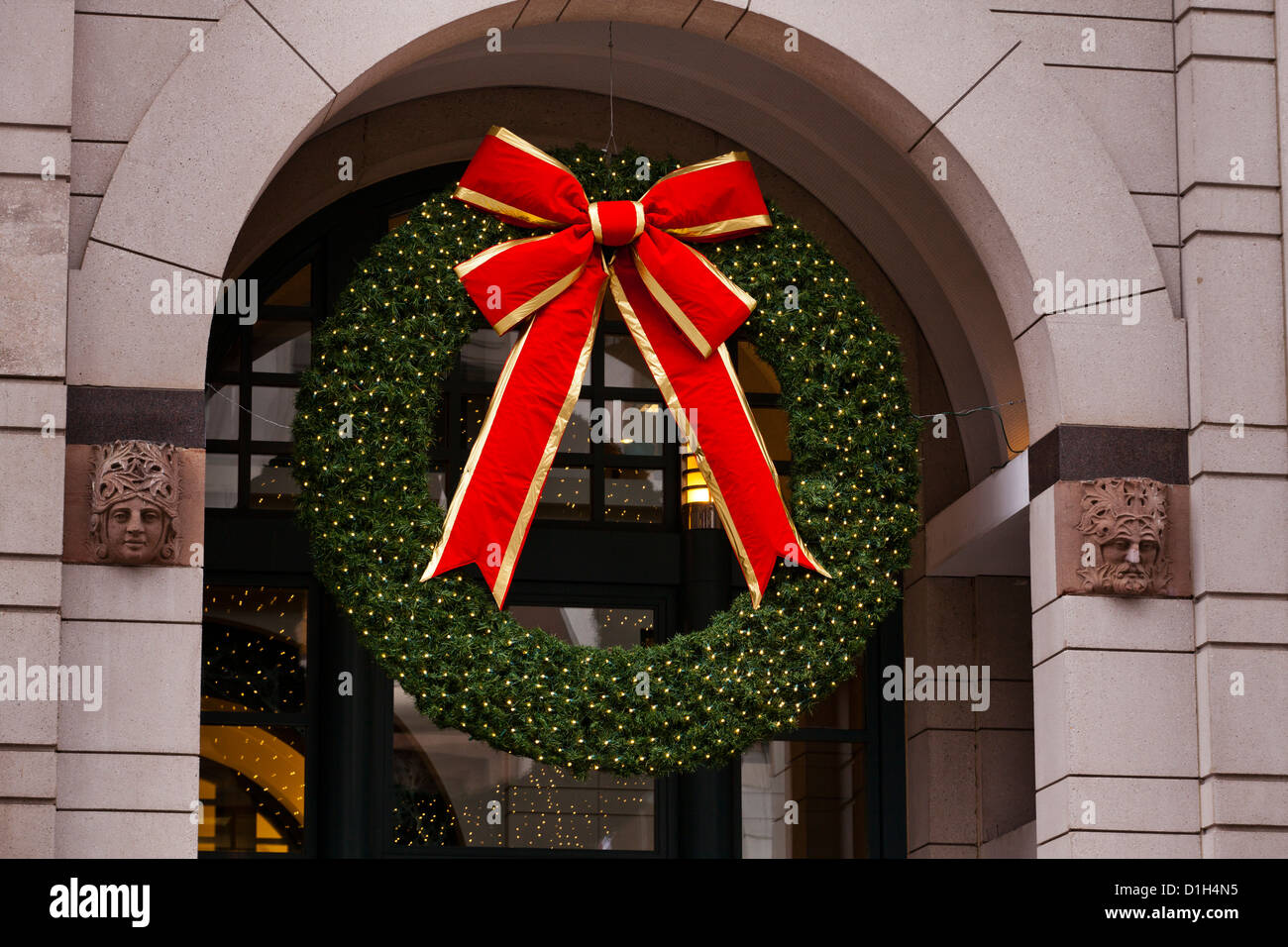 Christmas wreath over department store entrance - USA - Stock Image