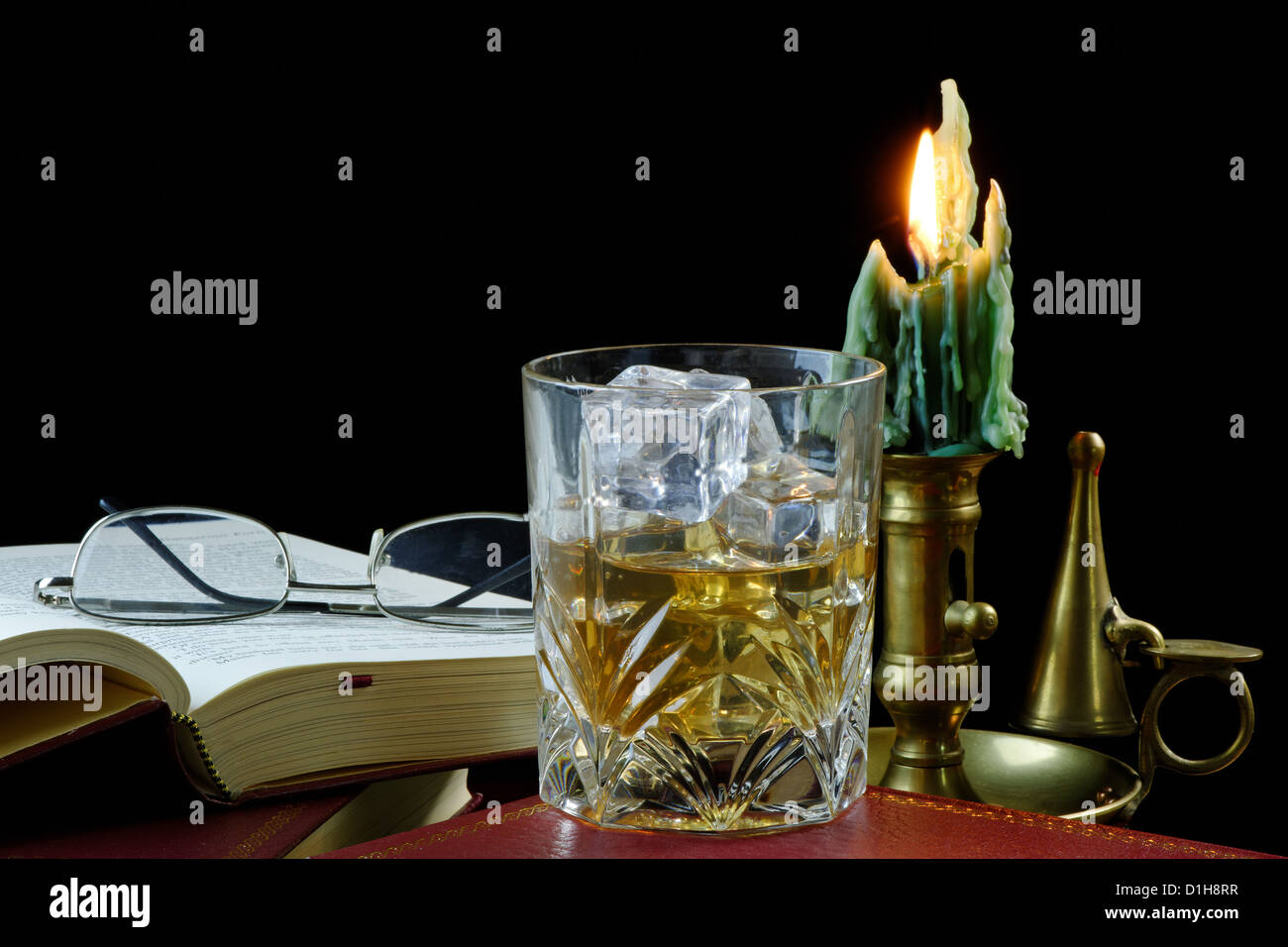 A glass of whisky with ice standing on an antique book, with candle and glasses - Stock Image