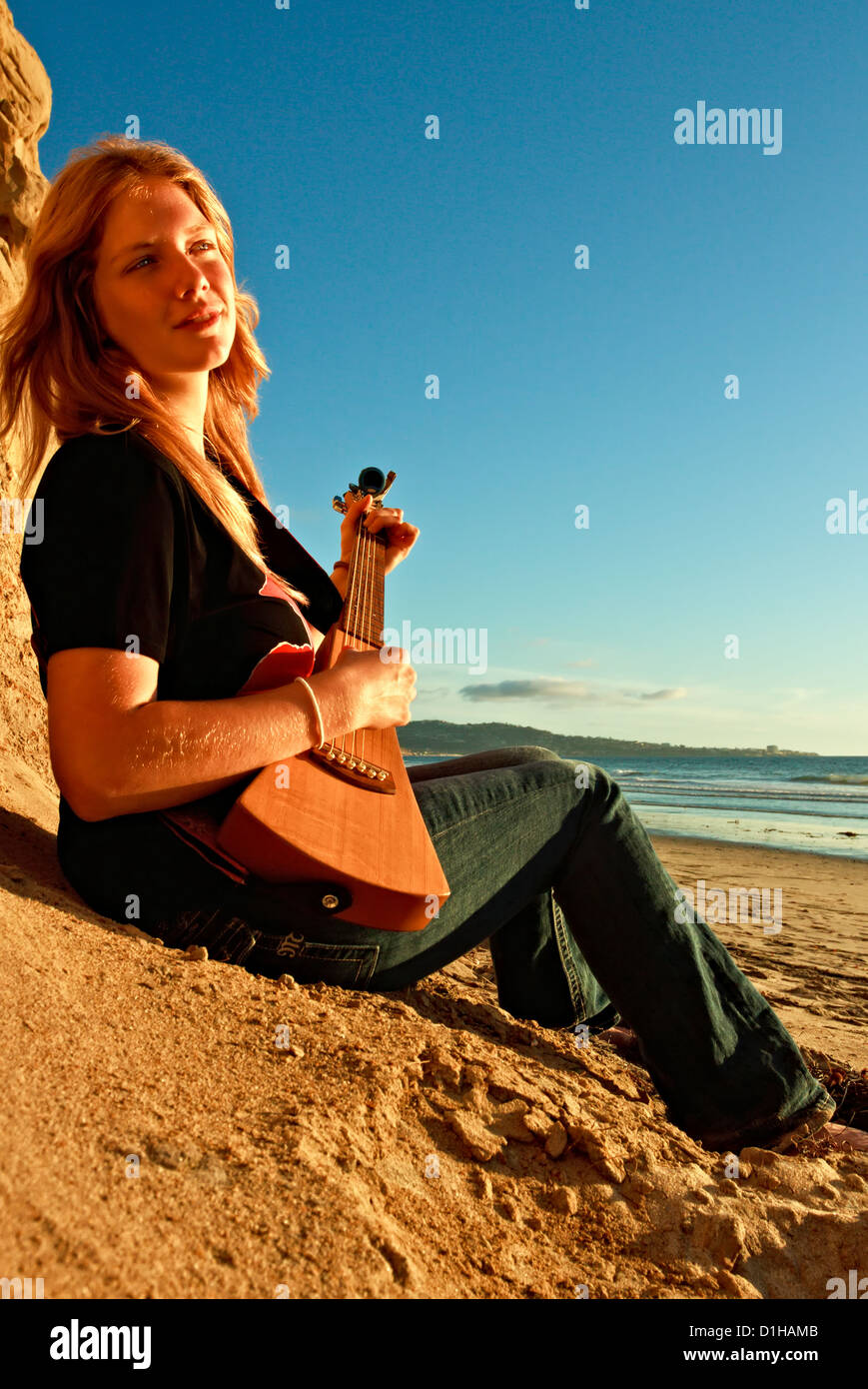 A beautiful young lady is captured, at the beach, while playing guitar. - Stock Image