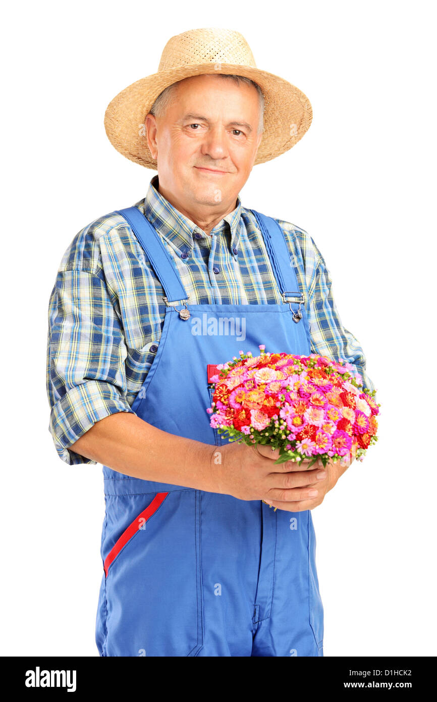 Mature gardener with panama hat holding a bunch of flowers isolated on white background - Stock Image