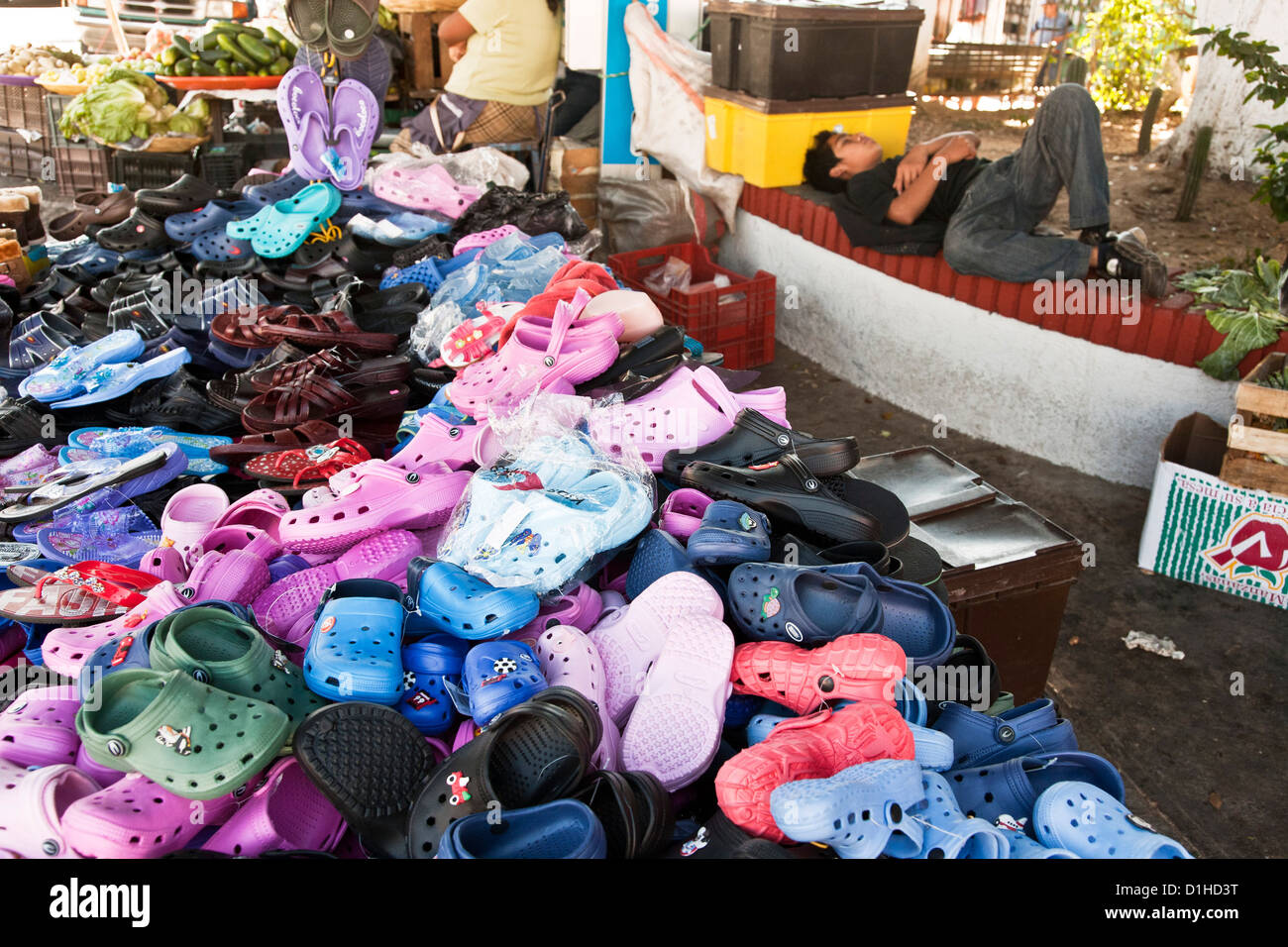 large bright pile of croc type shoes for sale with snoozing Mexican teen salesman taking a break mercado La Merced - Stock Image