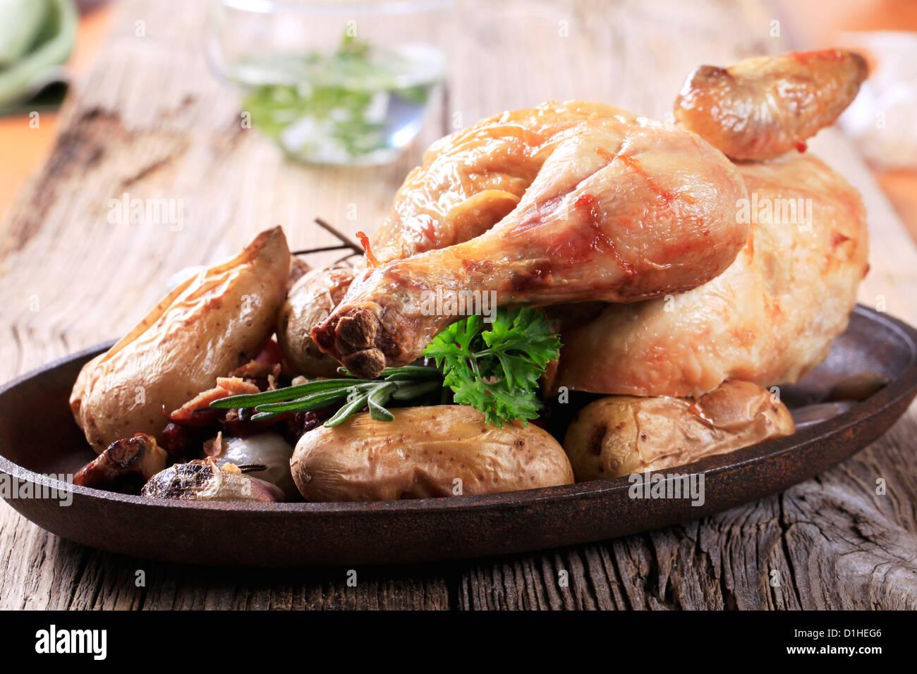Roast chicken and potatoes on cast iron platter Stock Photo