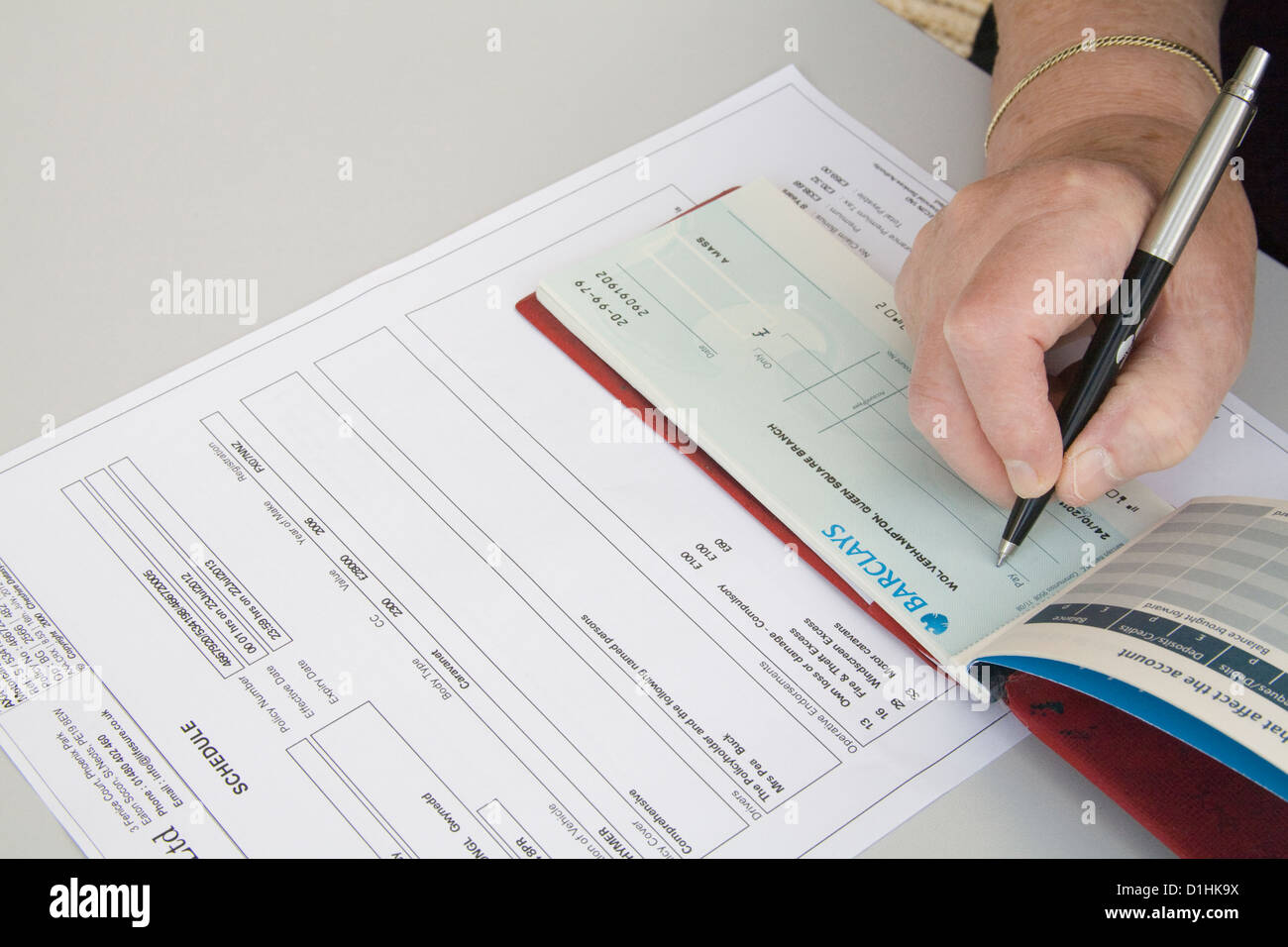 Close up pensioner writing cheque for car insurance renewal - Stock Image