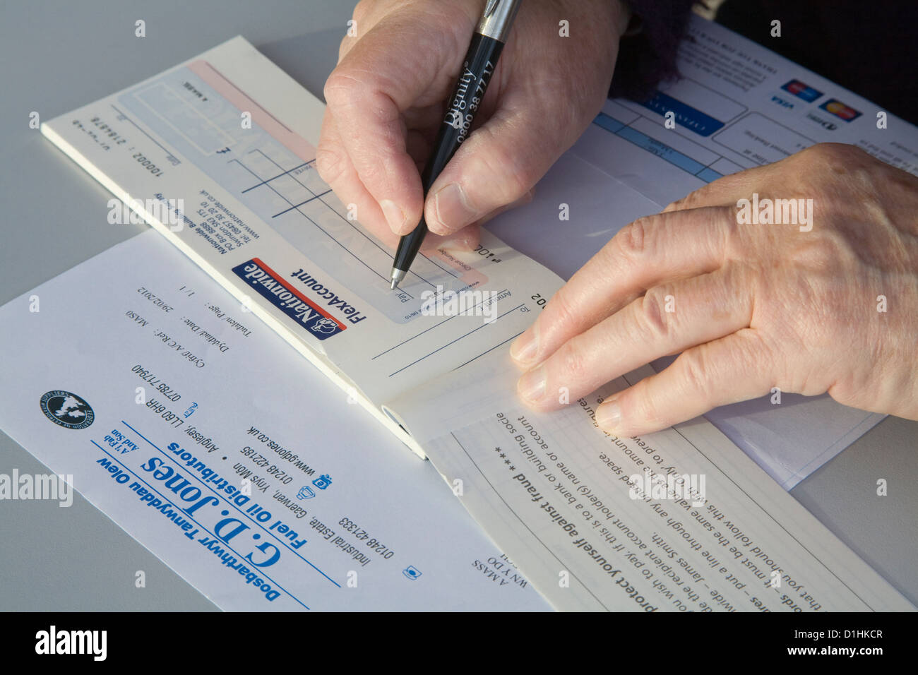 Close up pensioner writing cheque to pay oil heating bill - Stock Image