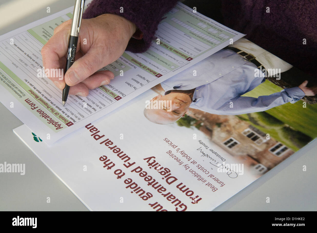 close up pensioner completing pre paid funeral plan application form