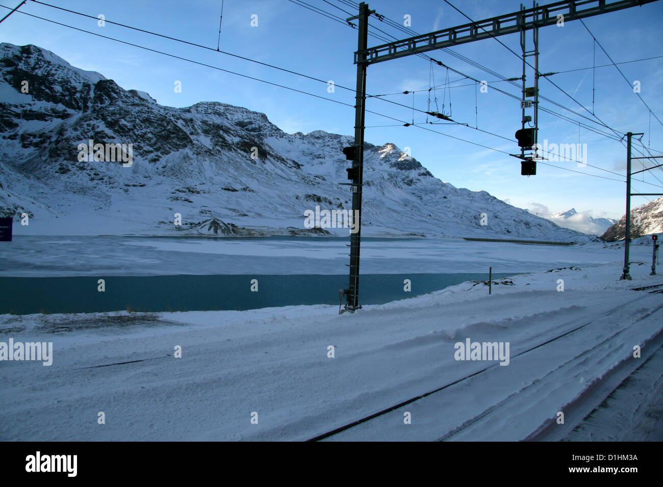 A very nice winter landscape from Bernina Express, of railraod near a frozen lake in Pontresina, Alp Grum, Switzerland - Stock Image