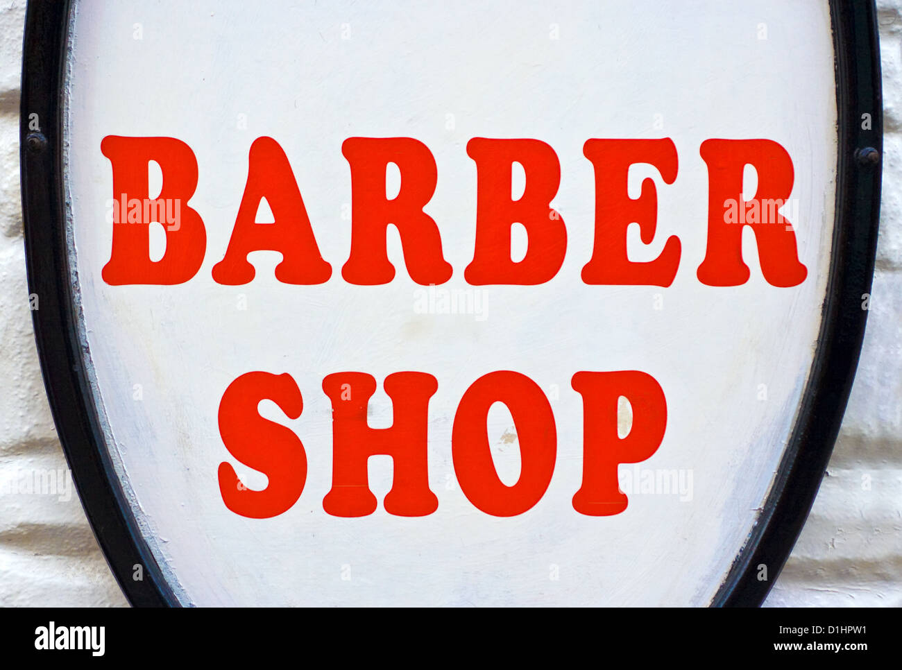 A Barber Shop sign with red letters and a white background - Stock Image