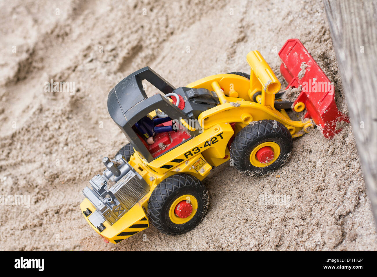 Bulldozer - a child's toy moves sand in a sand-pit - Stock Image