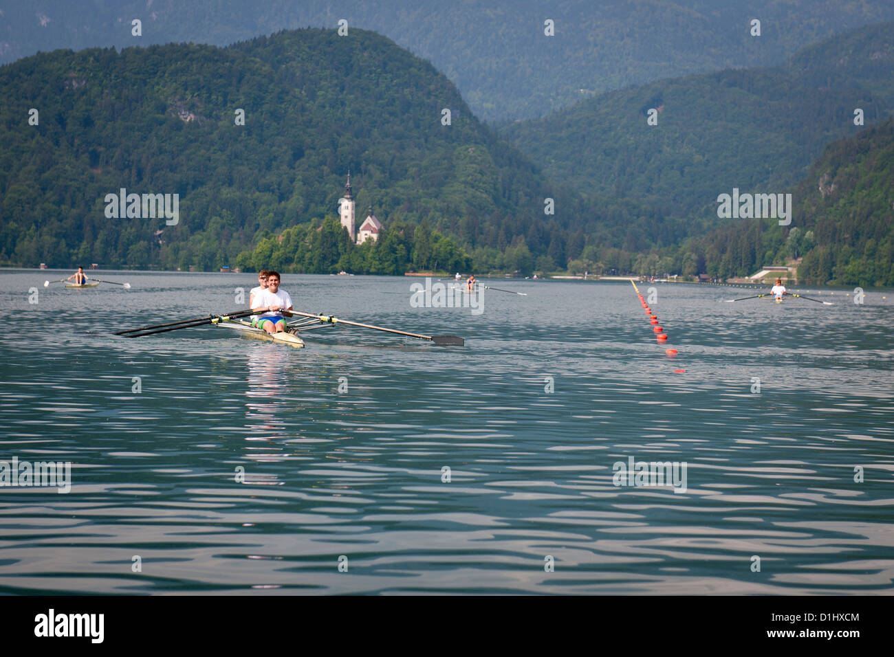 Lake Bled rowing course and the Church of the Assumption of Mary, Bled island, Slovenia - Stock Image