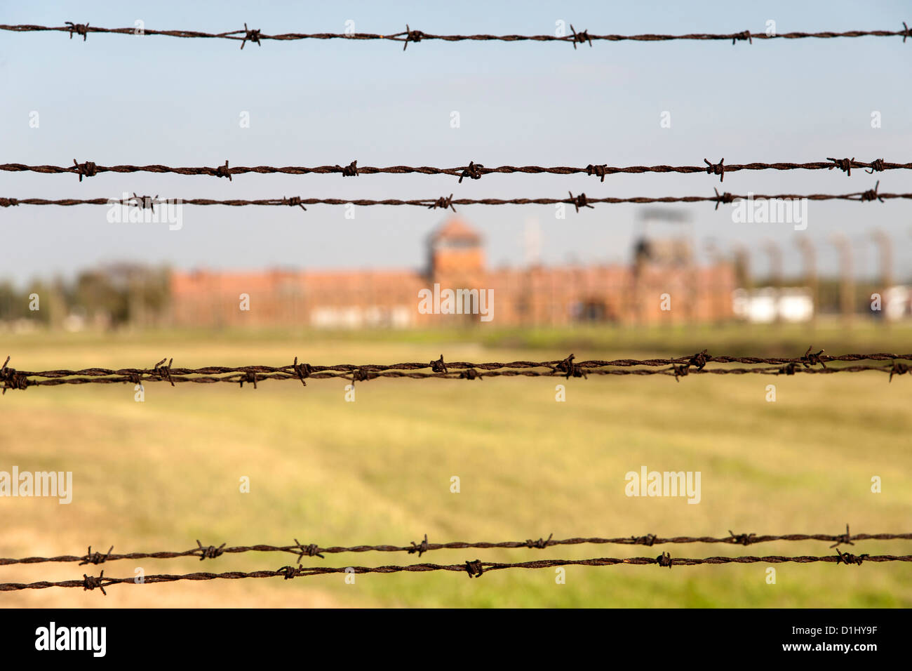 Barbed-wire fencing and buildings at the museum of the former Auschwitz II–Birkenau concentration camp in southern Stock Photo