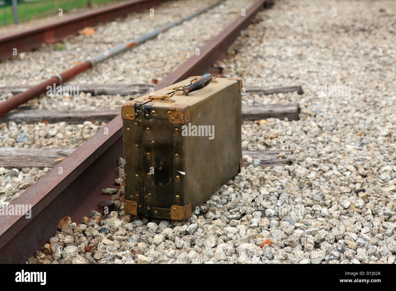 Old travel suitcase by the side of the railroad tracks. - Stock Image