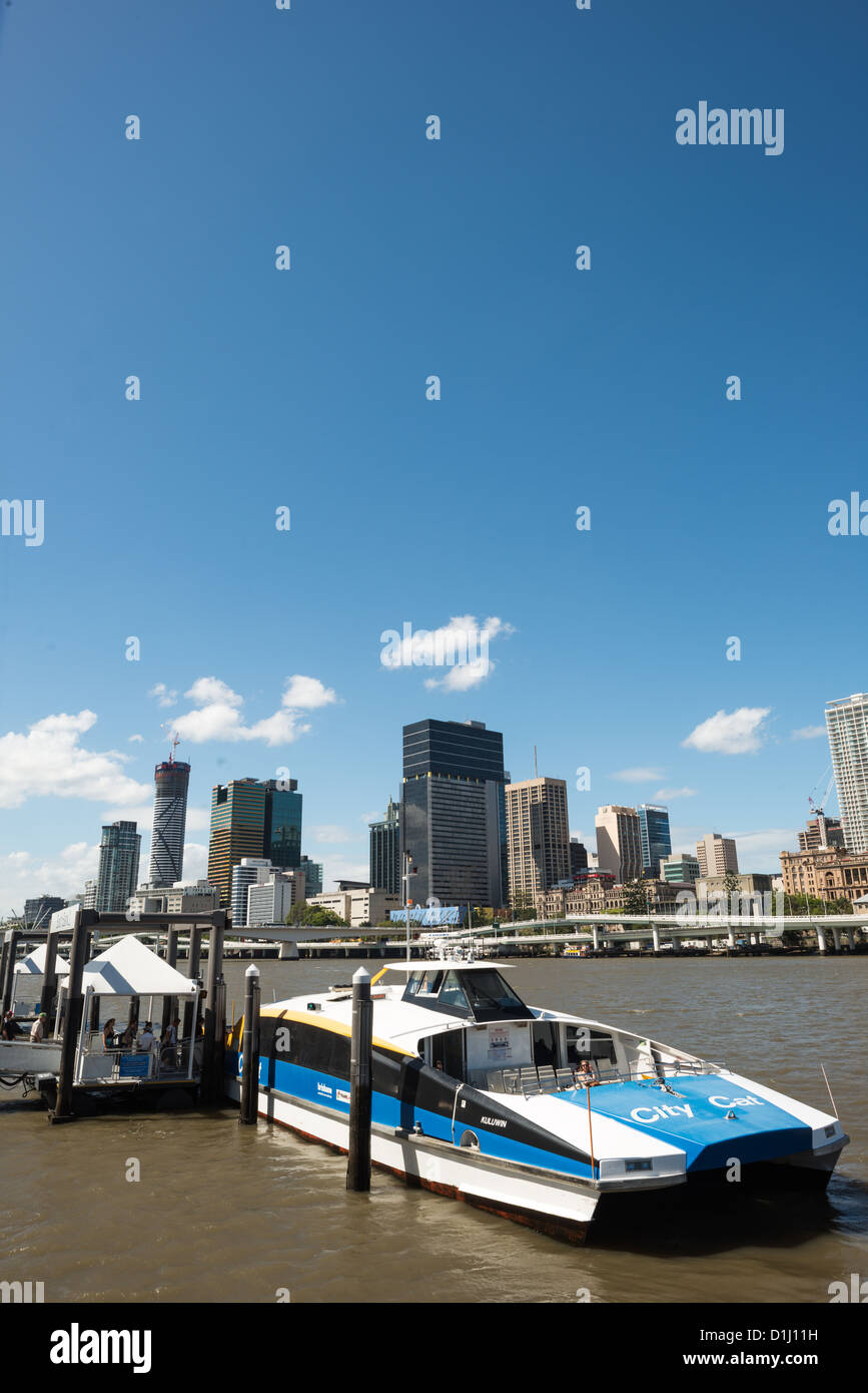 A Citycat ferry pulled up to a ferry terminal at South Bank, with the Brisbane city skyline in the background from - Stock Image