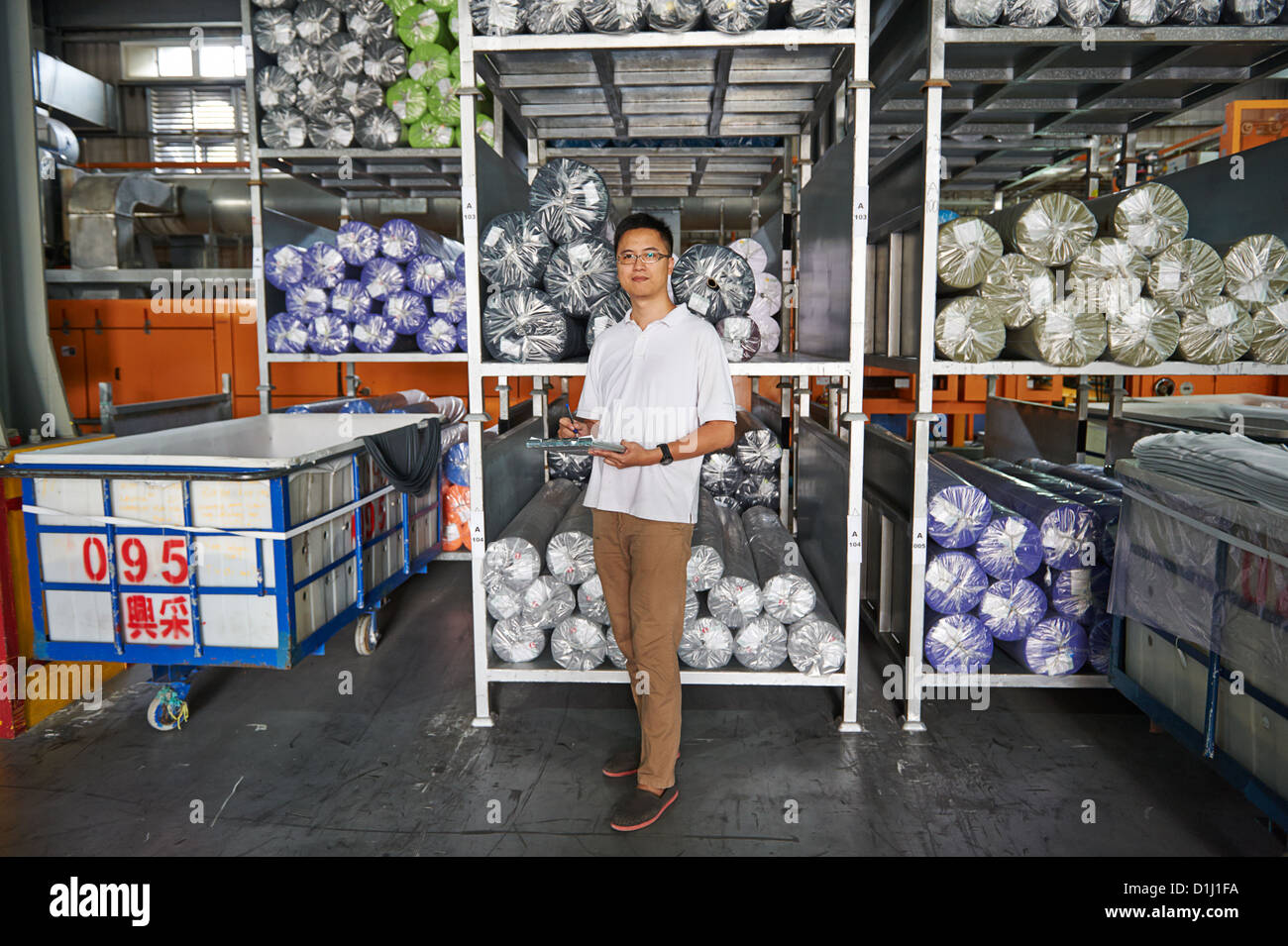 A manager with a clipboard stands next to a pallet of roller fabric - Stock Image