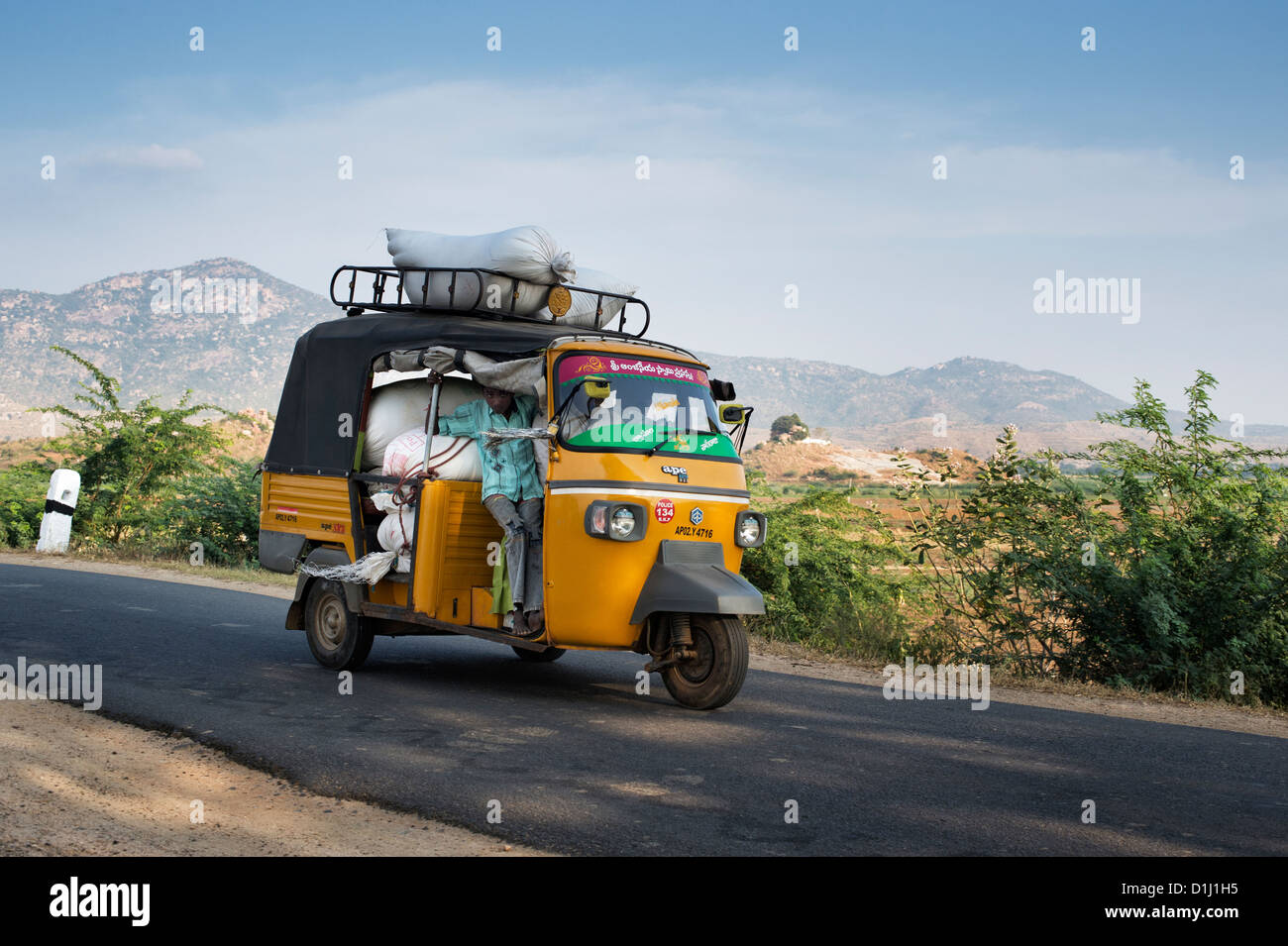Indian auto rickshaw overloaded with sacks of rice on a country road. Andhra Pradesh, India - Stock Image