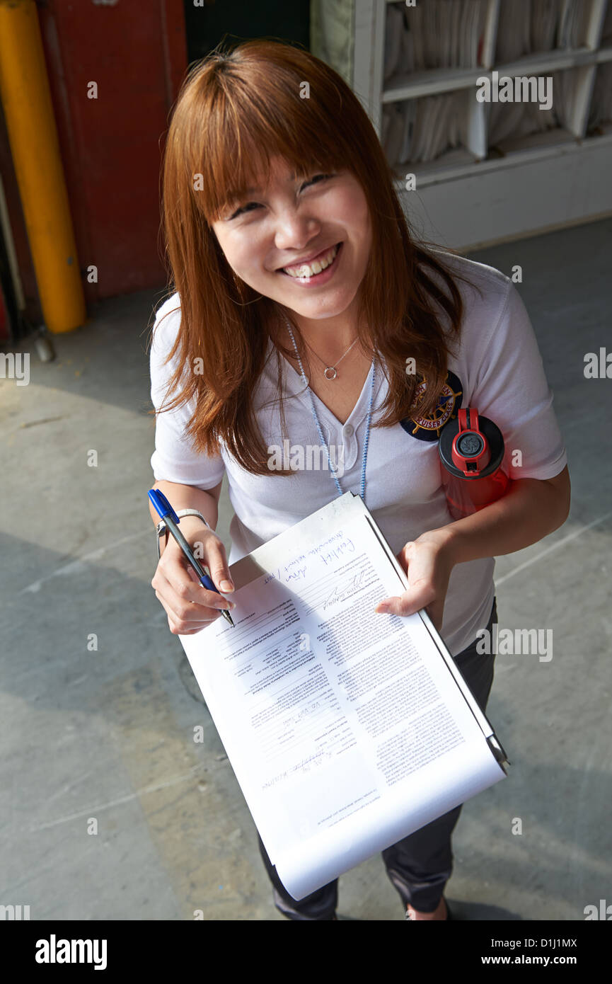 A girl holds a clipboard and smiles cheerfully - Stock Image