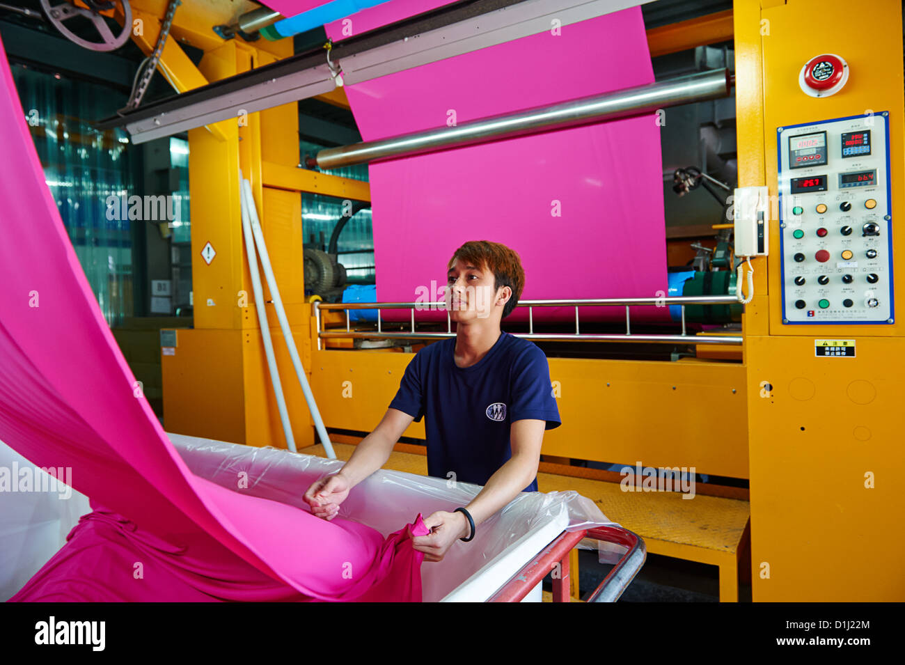 Workers pull and inspect newly pressed pink fabric into bins - Stock Image