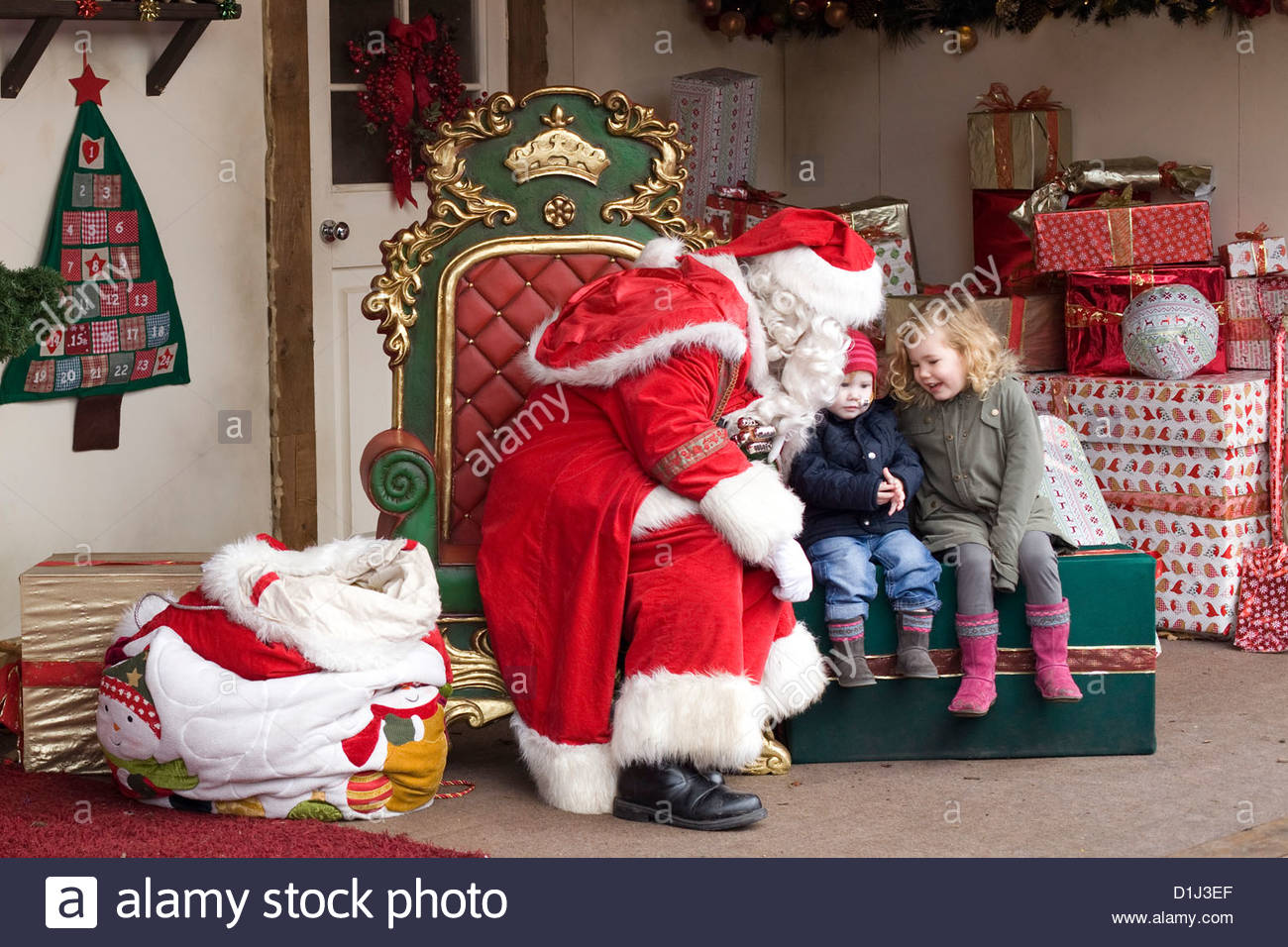Father Christmas Giving Presents To Children In Santas Grotto London England