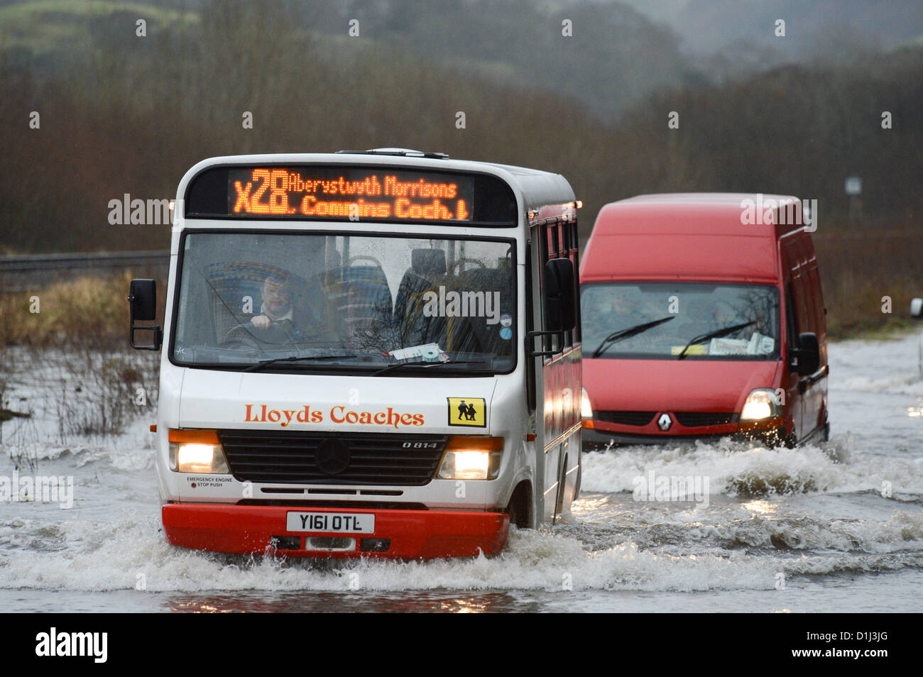Derwenlas, Ceredigion Wales UK. Monday 24 December 2012. Cars driving through floodwaters on the A487 trunk road - Stock Image