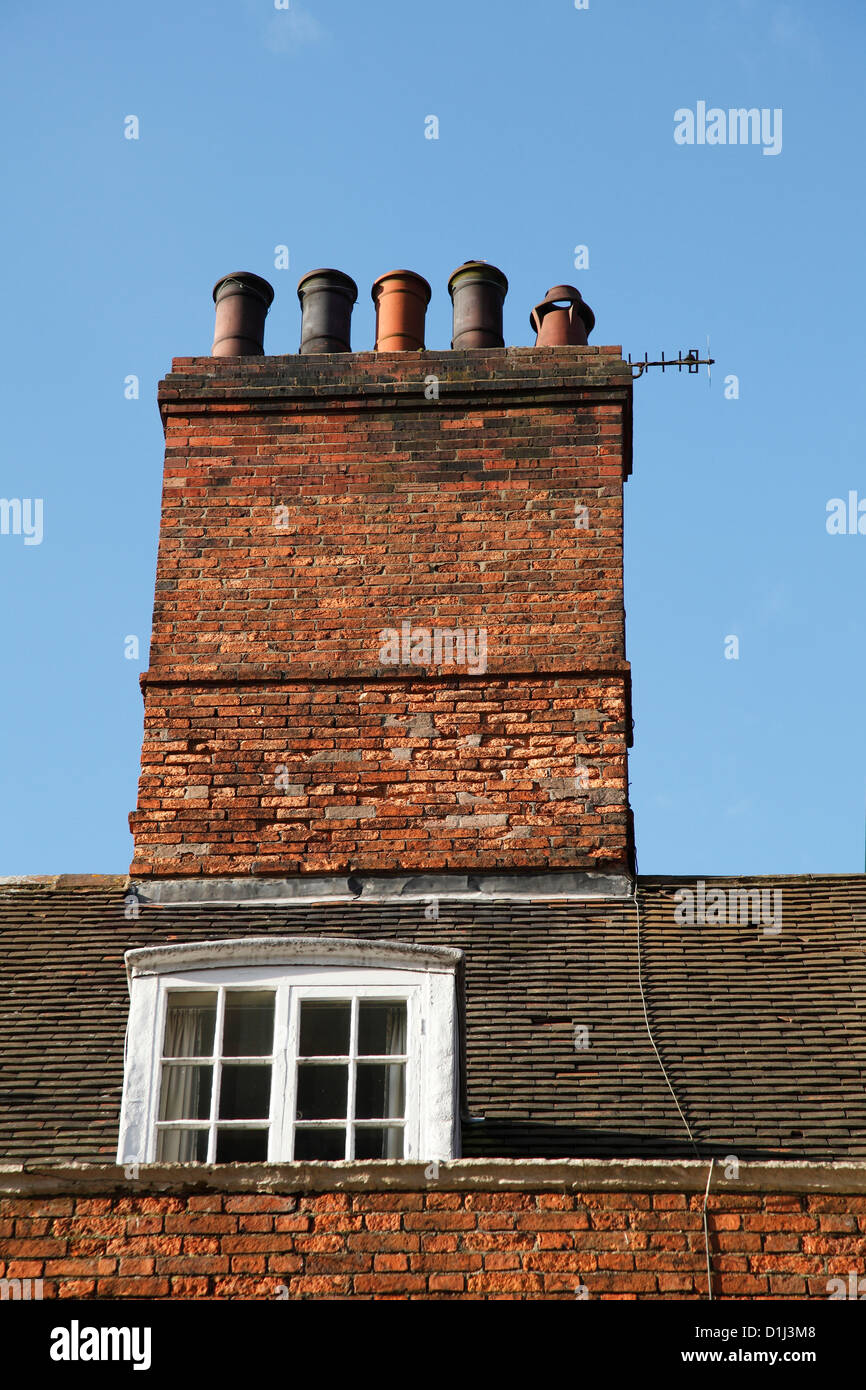 A chimney stack and attic window on a house in the U.K. - Stock Image