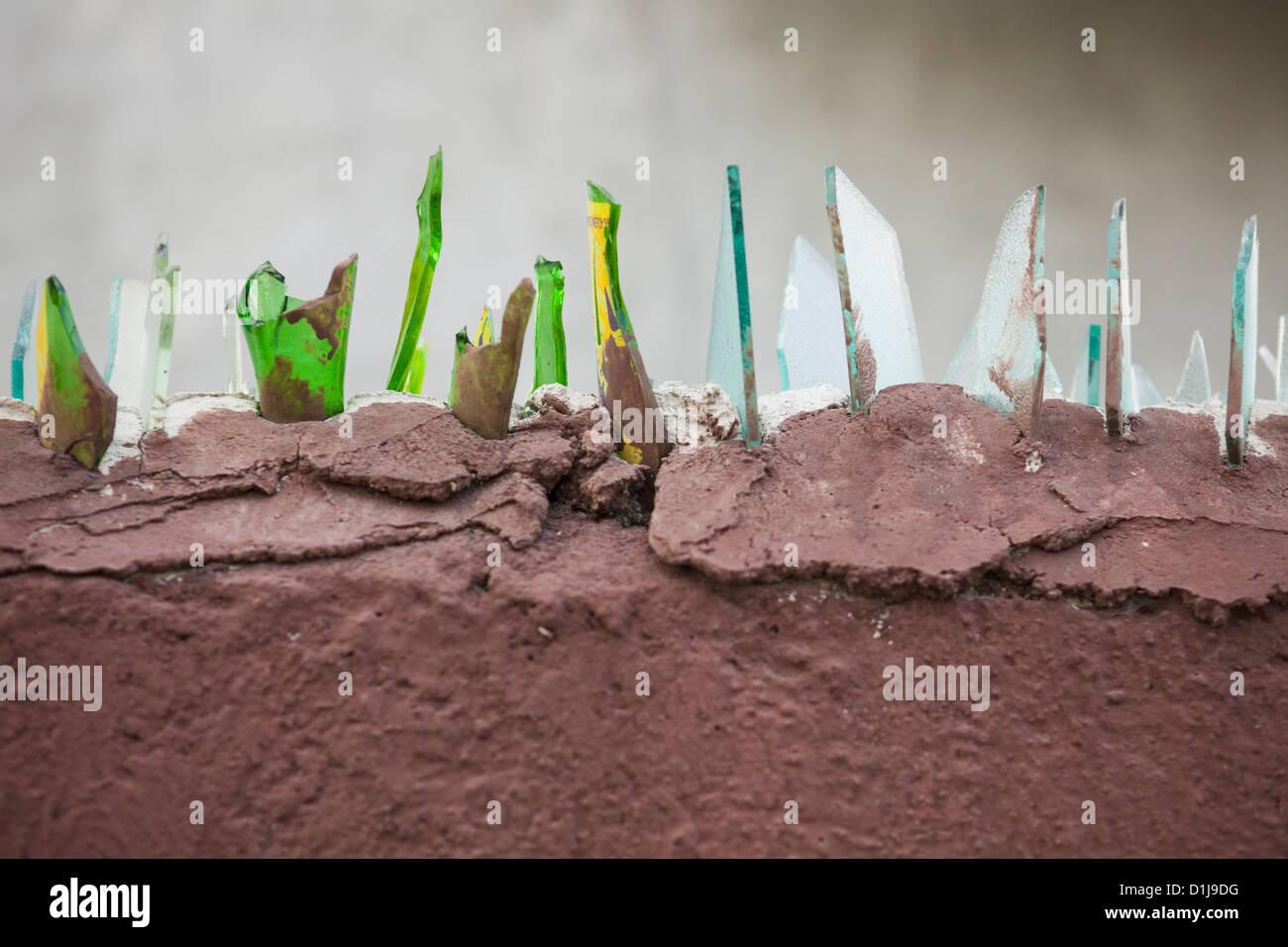 Broken Glass on Top of Wall for security, Yucatan Peninsula, Cancun, Quintana Roo, Mexico - Stock Image