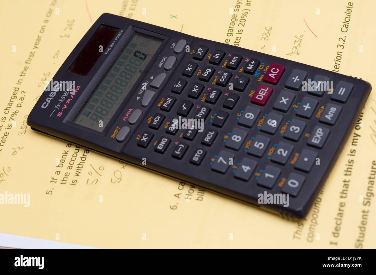 Scientific calculator on student school work. - Stock Image