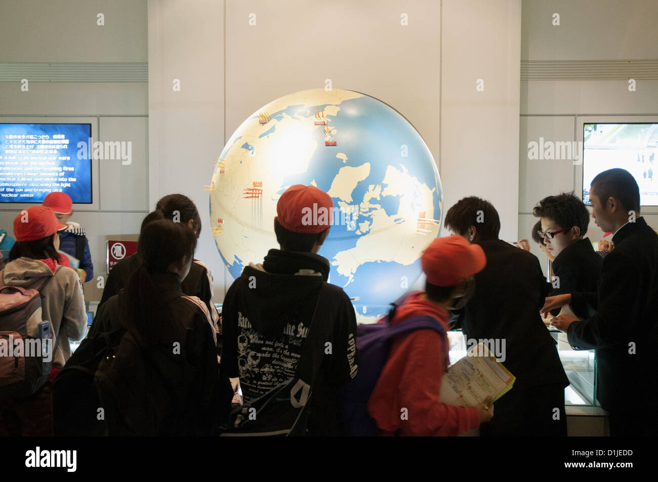 Japanese schoolchildren gather around a display in the Peace Memorial Museum at Hiroshima - Stock Image
